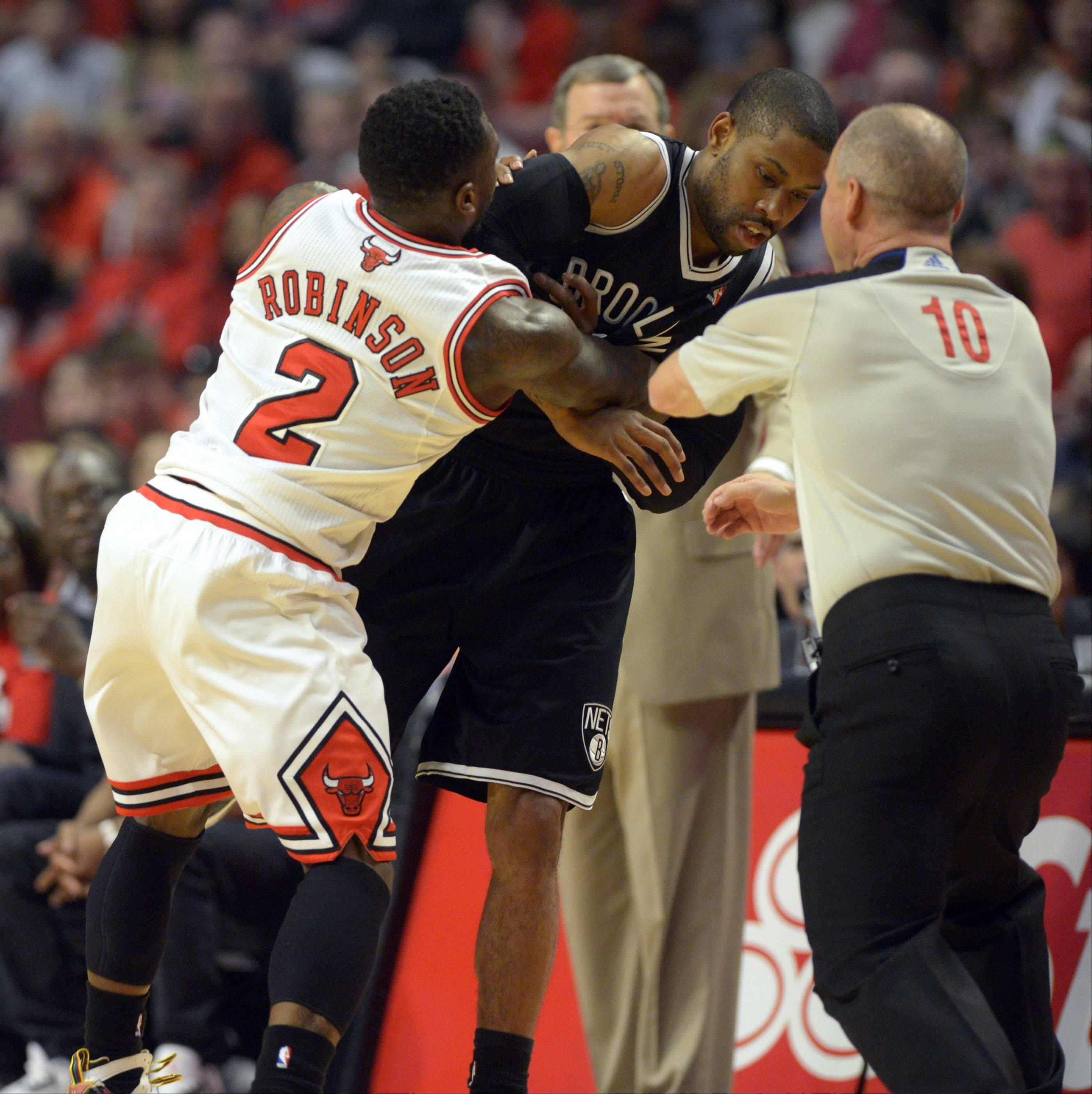 The Bulls Nate Robinson, left, and Brooklyn's C.J. Watson mix it up after fighting for the ball in the first half Saturday during game 4 of the first round playoff game against the Brooklyn Nets at the United Center. The Bulls won in triple overtime 142-134