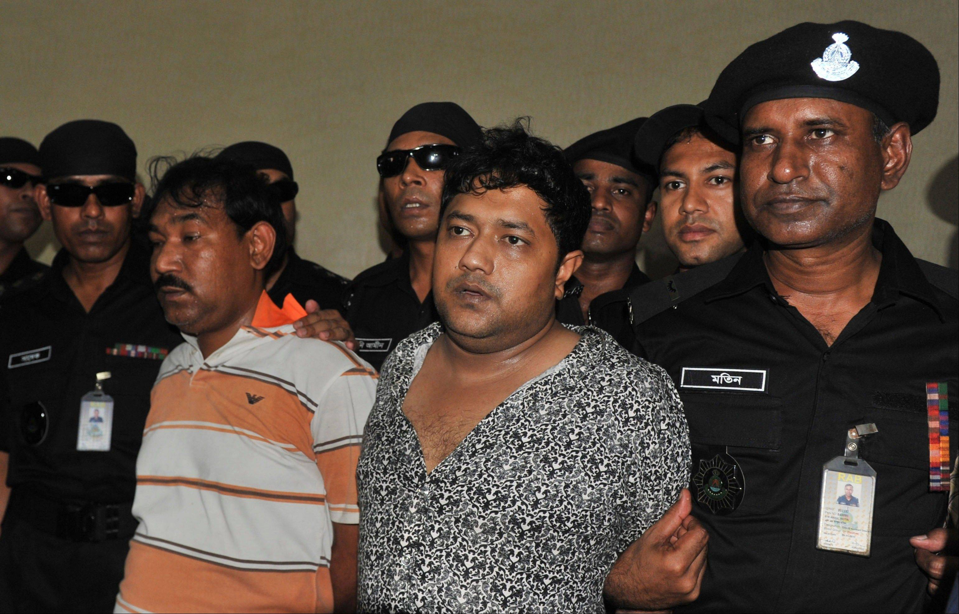 Mohammed Sohel Rana, centre right, the fugitive owner of an illegally-constructed building that collapsed last week in Bangladesh, killing some 377 people, is paraded by Rapid Action Battalion commandoes for the media along with an unidentified alleged accomplice, left, in Dhaka, Bangladesh, Sunday.