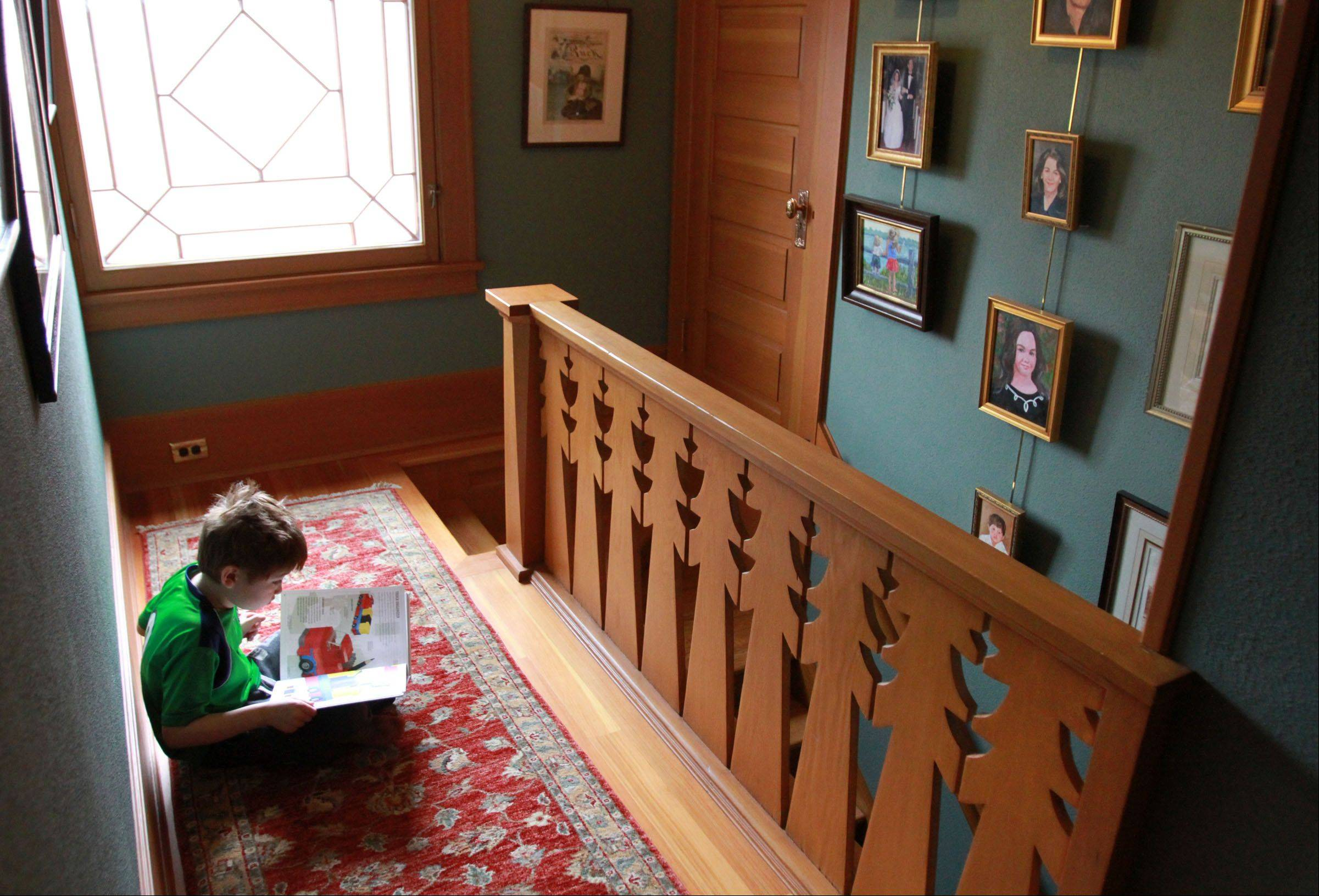 Mark Donovan and Mary Ludgin's son, Cooper Donovan, 7, reads by the tree-design staircase rail designed by Frank Lloyd Wright.