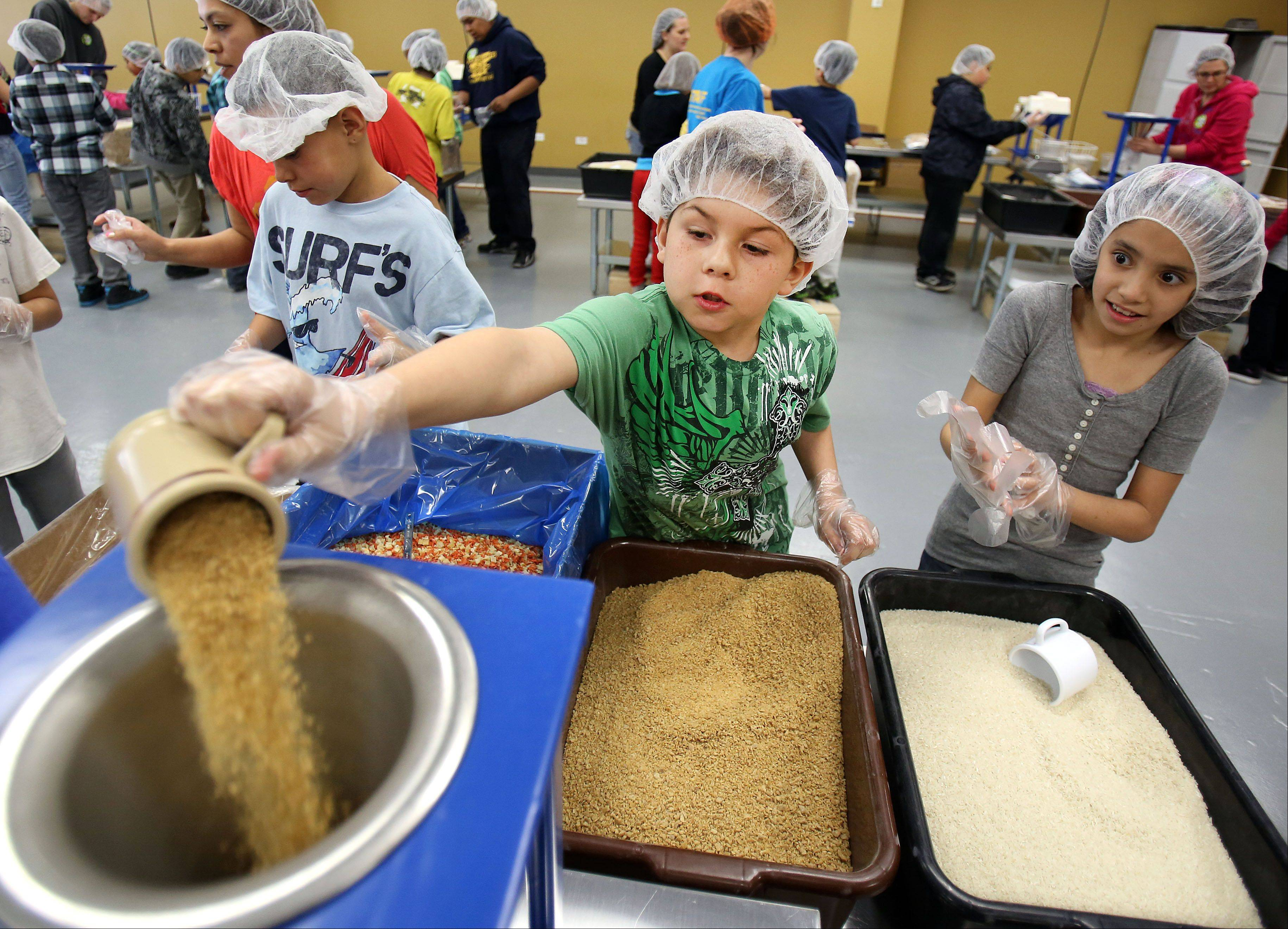 4th grader student Chris Rosado from W.J. Murphy School in Round Lake helps make meals at Feed My Starving Children in Libertyville Thursday. About 100 fourth graders and parents participated.