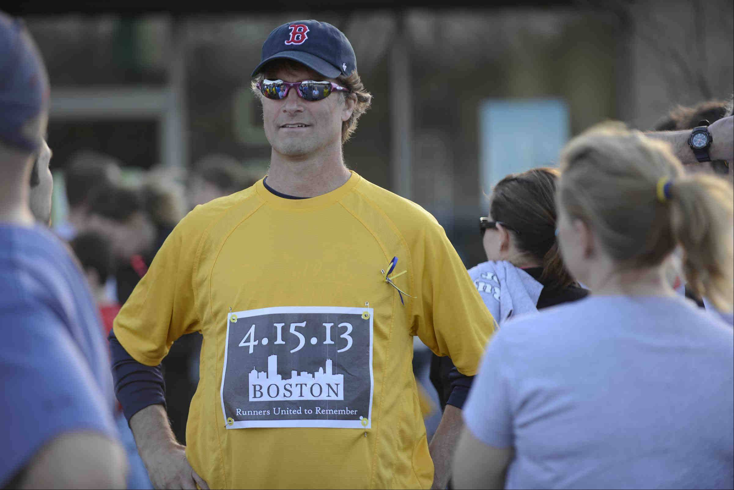 Lance Adams of St. Charles wears a Boston cap and a commemorative race bib as he gathers with other runners Monday evening for a benefit run to honor the Boston community that was the target of terrorists bombs. Dick Pond Athletics in St. Charles was one of hundreds of running stores across the country to hold the Runners For Boston event.