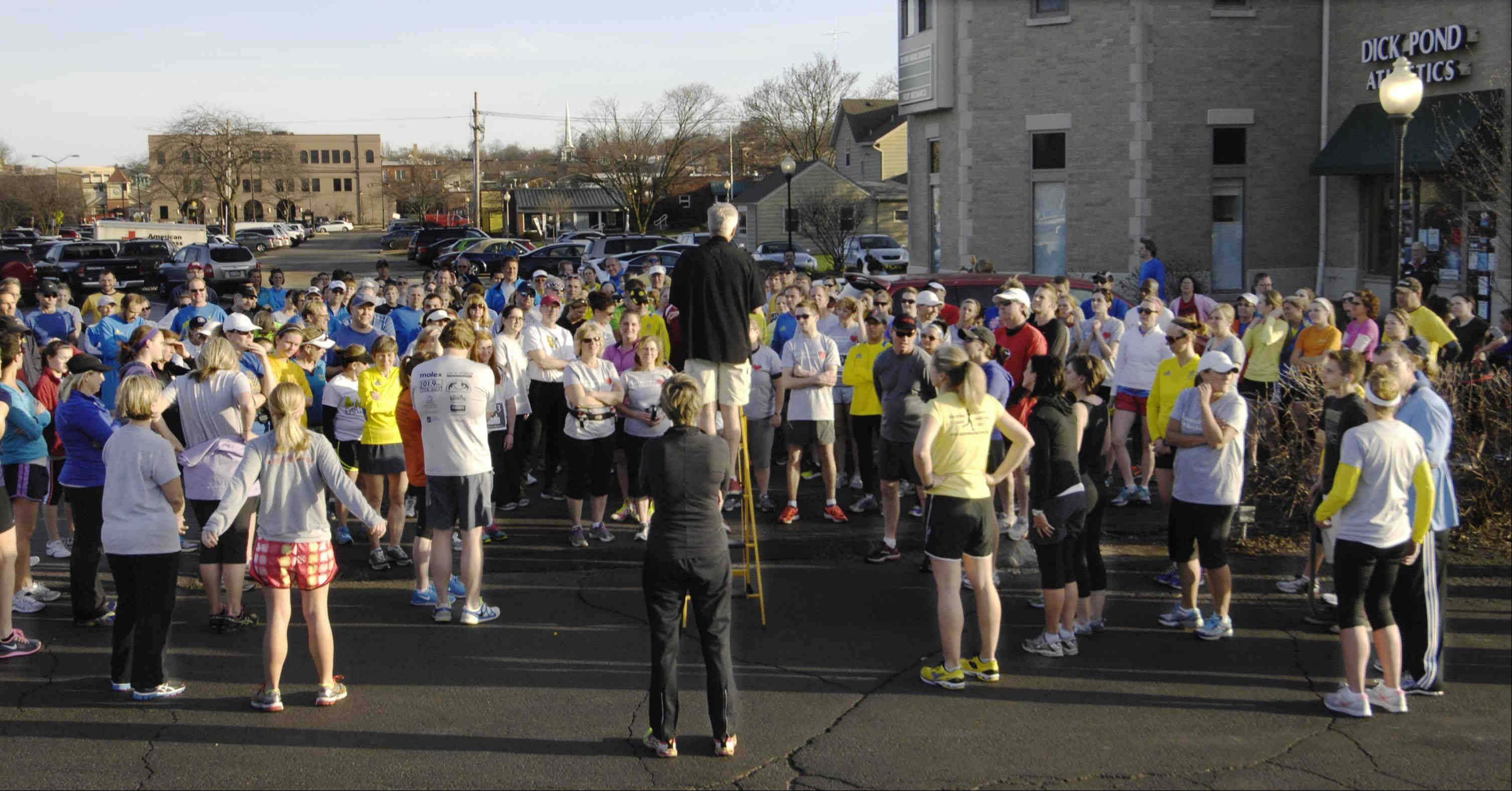 Dick Pond Athletics manager Glen Kamps stands on a ladder to organize dozens of runners Monday evening for a benefit run to honor the Boston community that was the target of terrorists bombs.