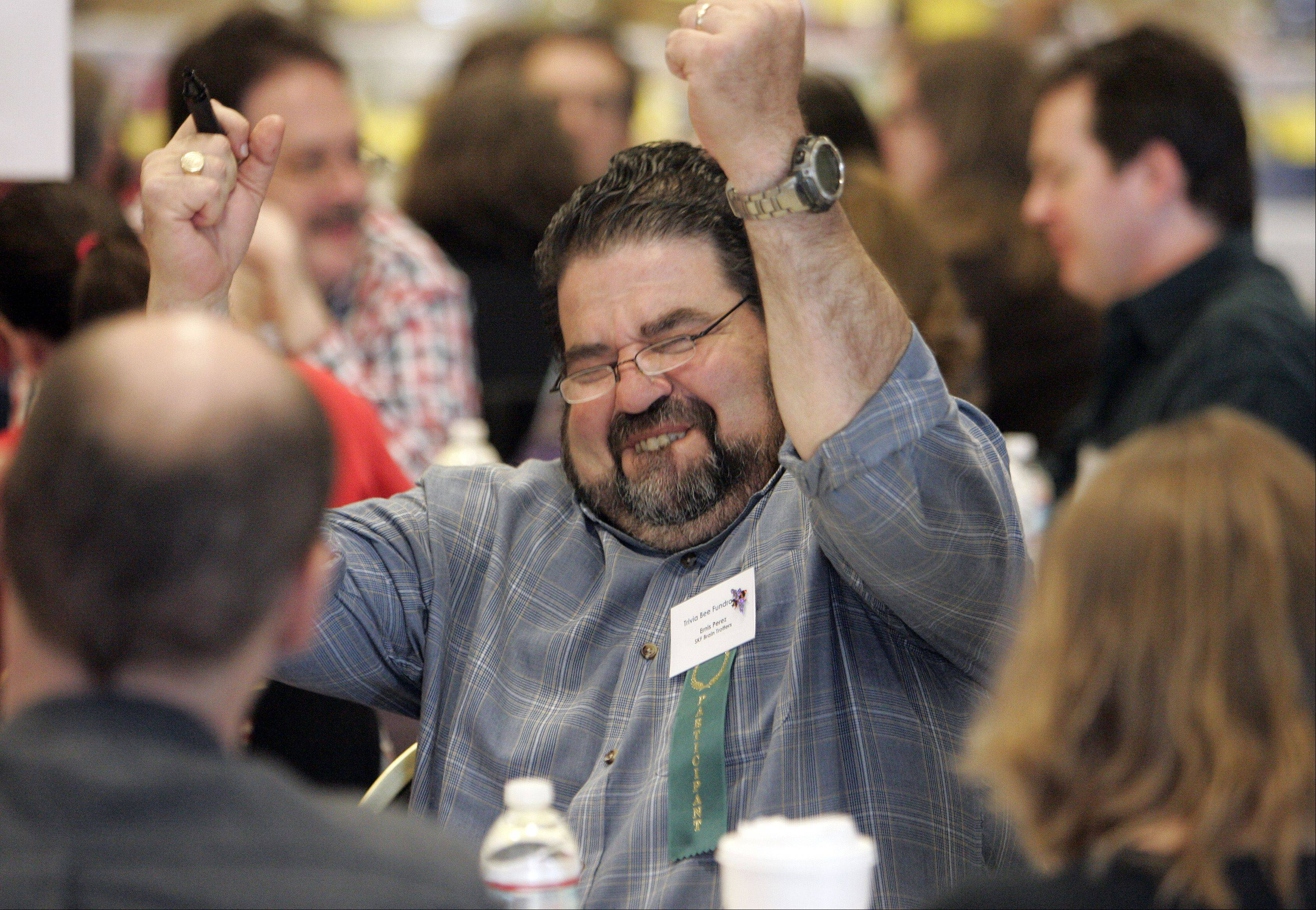 Ernis Perez of SKF Brain Trotters reacts after his team recorded a correct answer during the 16th annual Literacy Connection Trivia Bee Fundraiser Saturday at the Fox River Room Grand Victoria Casino in Elgin.