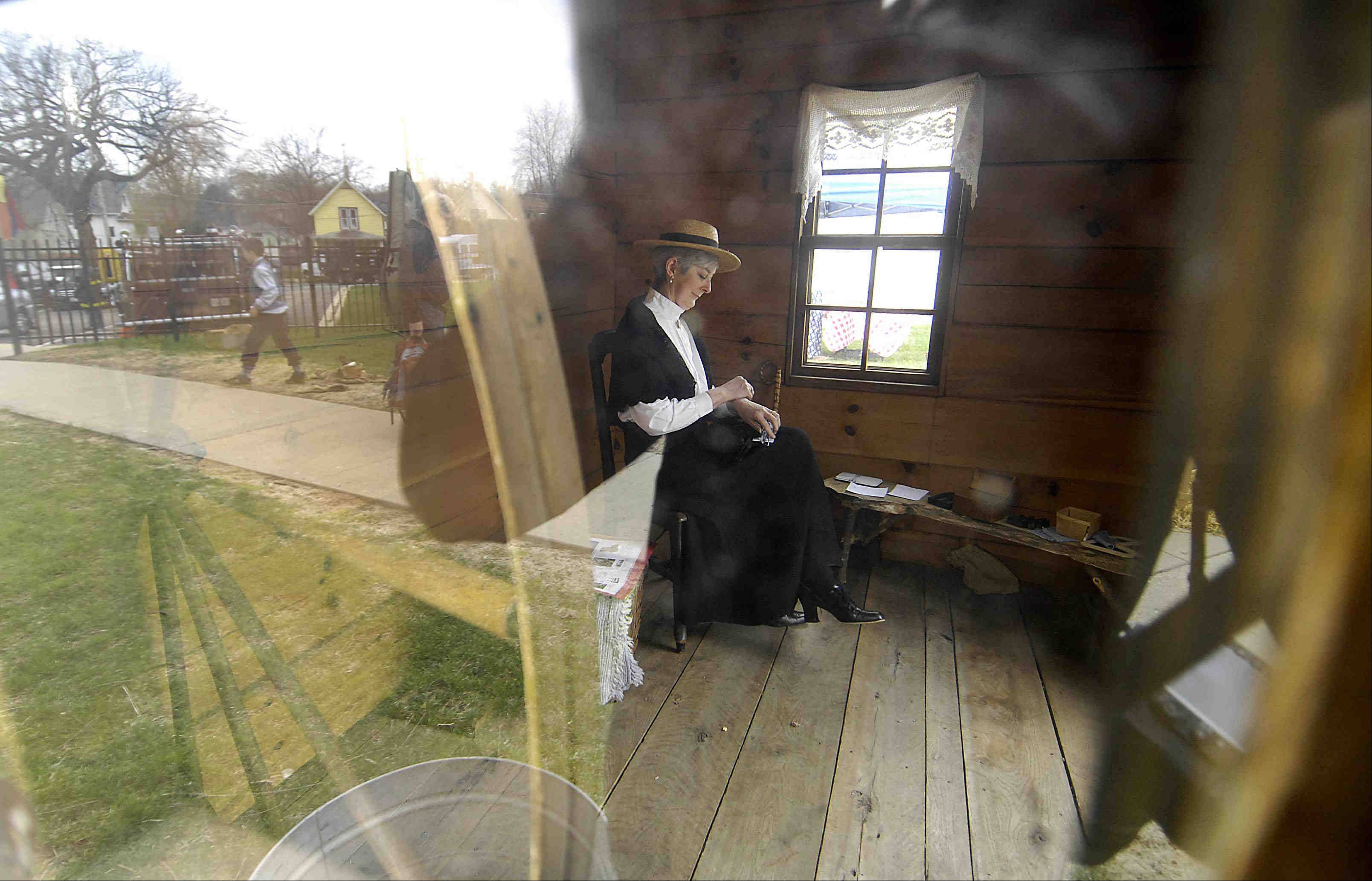 Seen through a small window, Linda Rock, of Elgin, sits inside a small schoolhouse Sunday at the ninth annual Elgin History Fair. She was playing the part of the school marm and waiting for visitors. The event featured chances to learn about making butter by hand, play with historical wooden toys and grind corn at the Elgin Historical Museum.