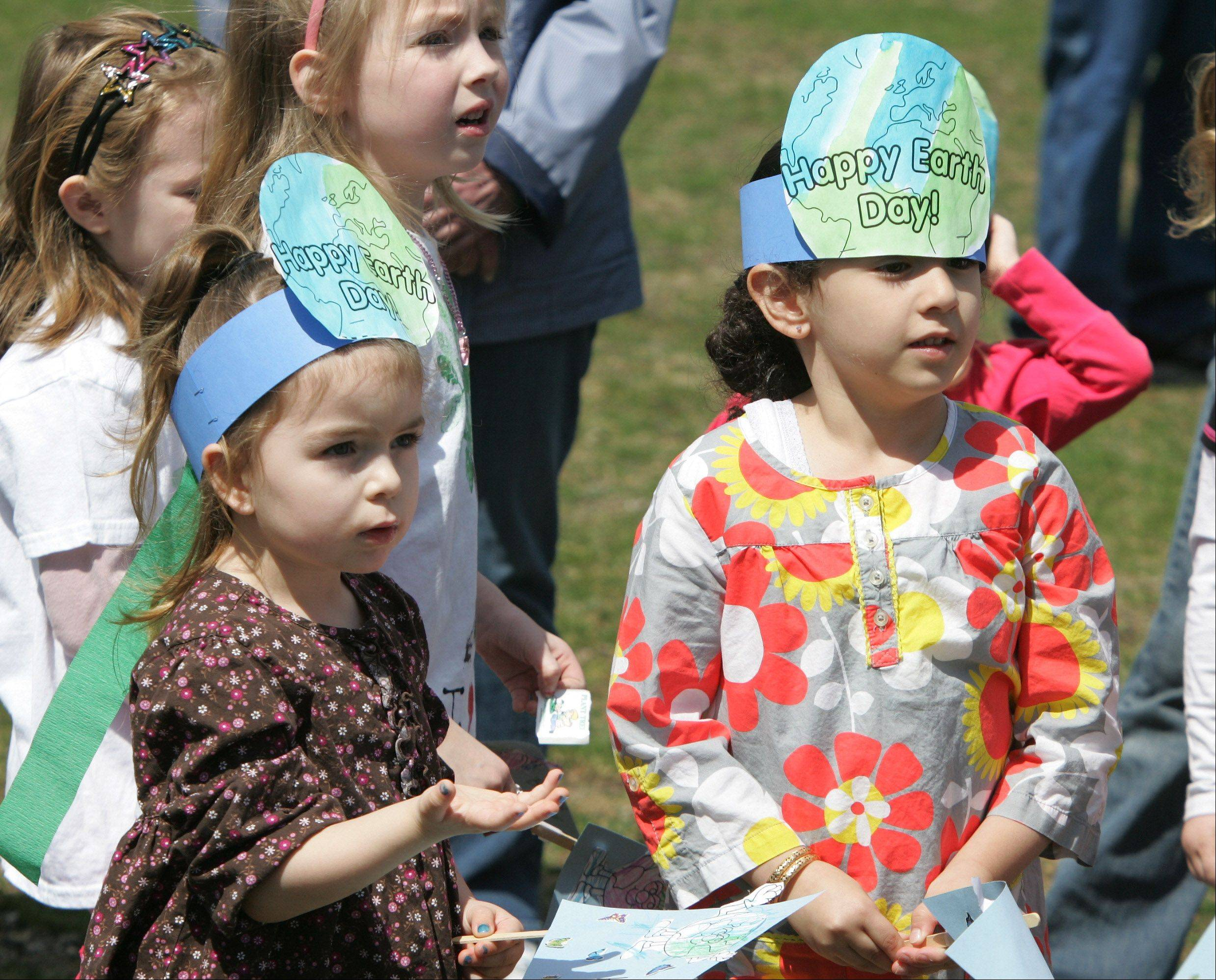 Preschoolers Dana Ustrnul, left, and Buthaina Rahaby, both 4, learn about growing trees during the Earth Day event at the Learning Center Preschool in the Mundelein Park District Monday. A white oak tree was planted and preschool children learned about Earth Day and Arbor Day.