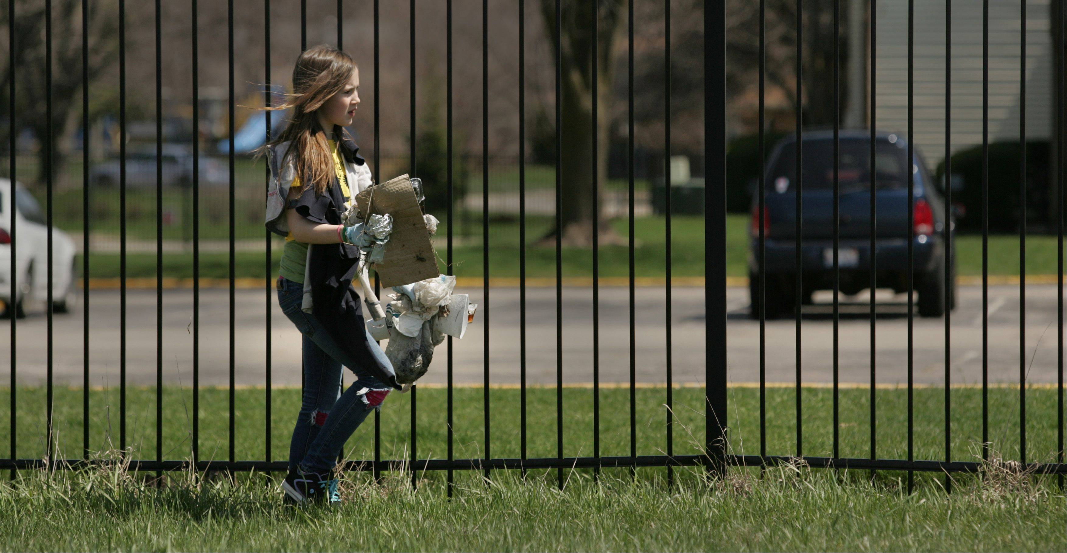 "Century Oaks sixth-grader Madison Kloss has about as much garbage as she can carry Monday while participating in the ""Pick it Up"" anti-litter campaign community clean up."