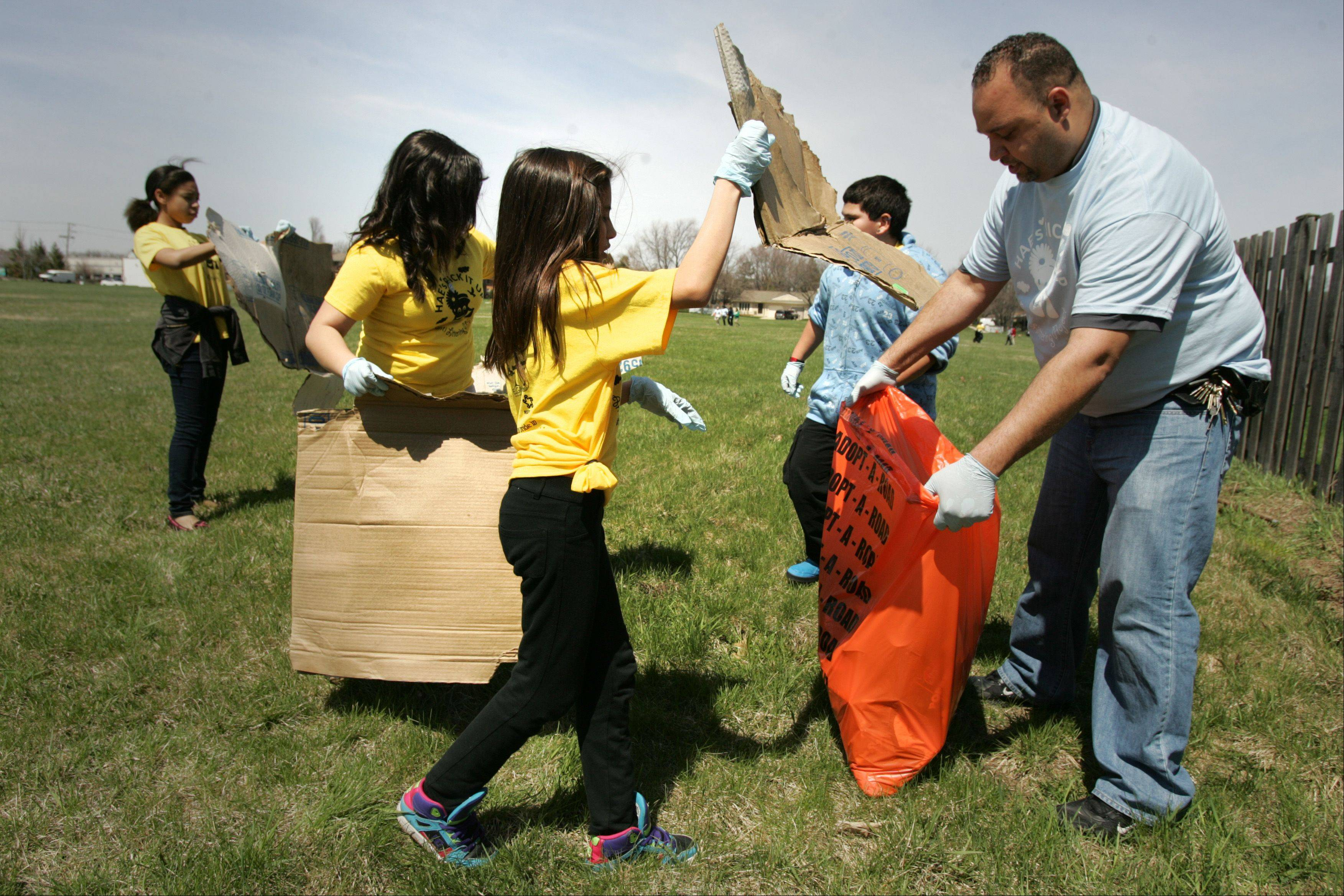 "Century Oaks sixth-graders Janet Antunez and Alondra Escobar help bag more garbage they found Monday while working with Elgin Police officer Rob Hartman during the ""Pick it Up"" anti-litter campaign community clean up. The Housing Authority of Elgin partnered with Century Oaks Elementary School thanks to a grant from the city of Elgin�s Sustainability Committee"