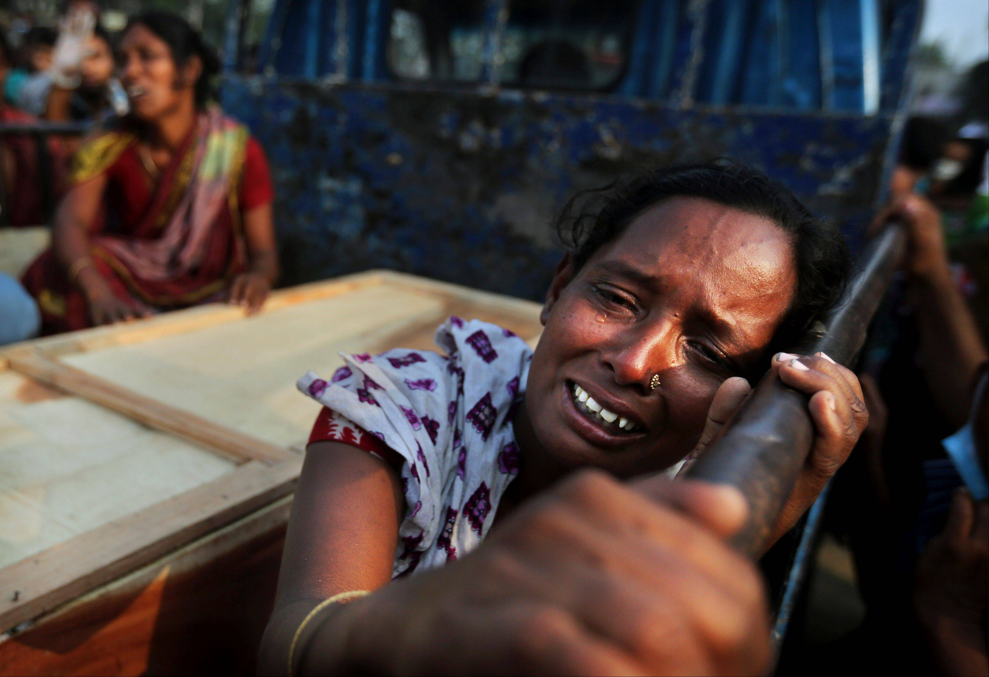A Bangladeshi woman weeps as she sits next to the coffin of a relative who died in a building that collapsed Wednesday in Savar, near Dhaka, Bangladesh, Sunday. A fire broke out late Sunday in the wreckage of the garment factory that collapsed last week in Bangladesh killing hundreds, with smoke pouring from the piles of shattered concrete and some of the rescue efforts forced to stop.