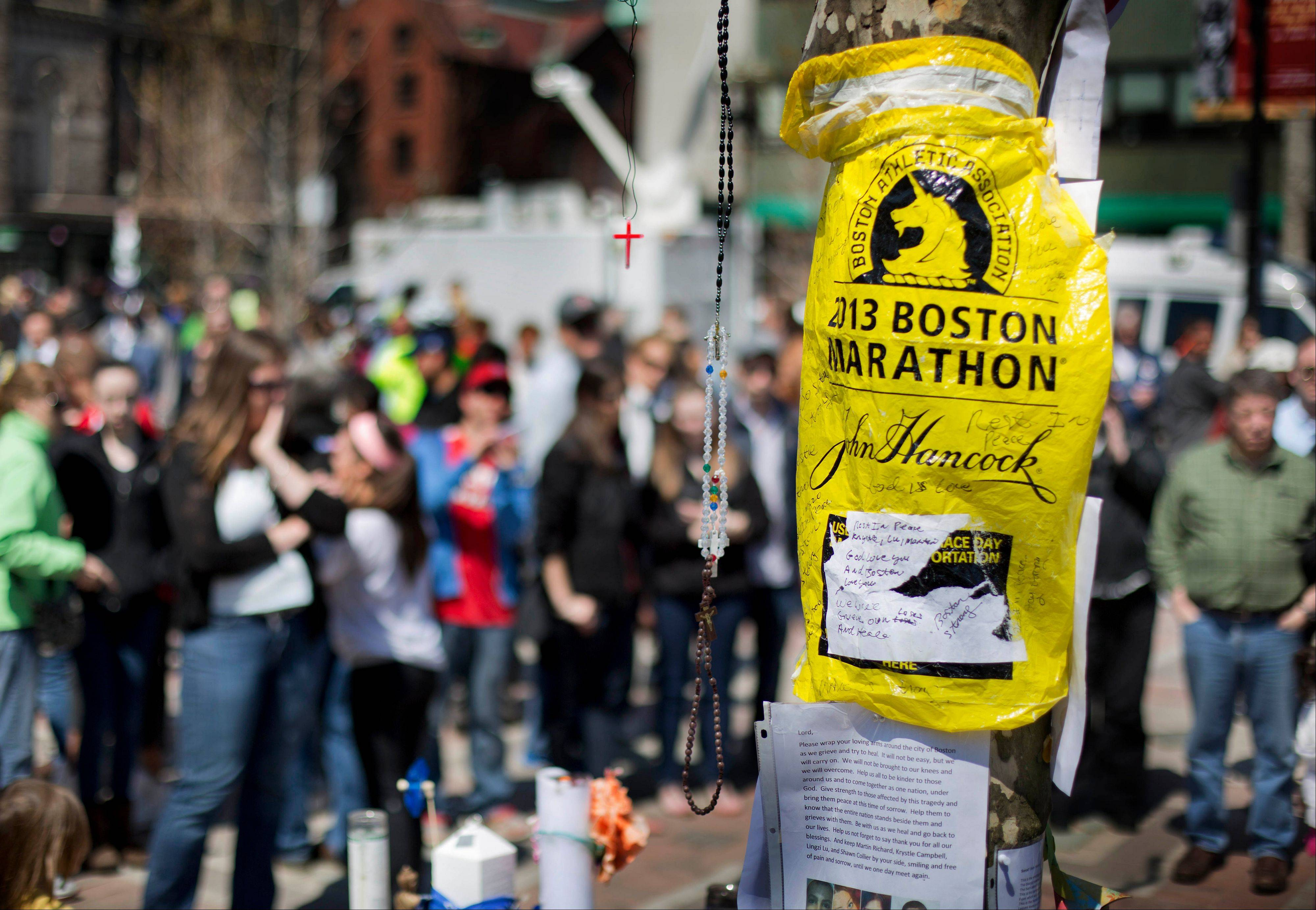 Visitors pause at a makeshift memorial in Copley Square for victims of the Boston Marathon bombings this past weekend in Boston.