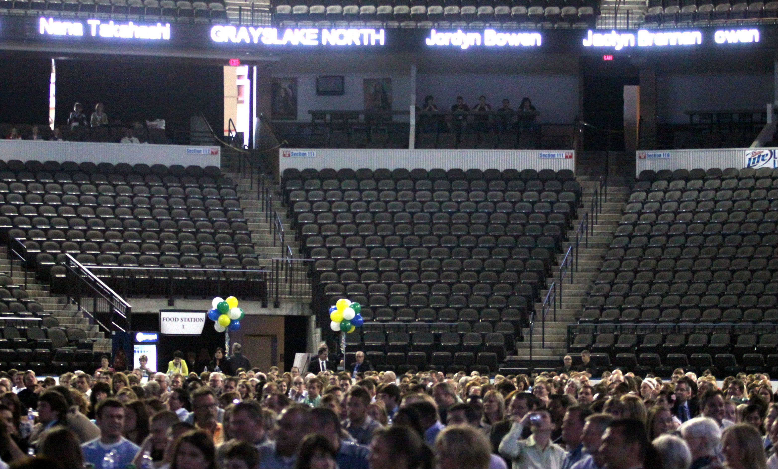 Student-athletes and their families participate during the Daily Herald Prep Sports Excellence Awards Ceremony at Sears Centre Arena in Hoffman Estates on Sunday. Each student's name was displayed on the ribbon scoreboard circling the arena.