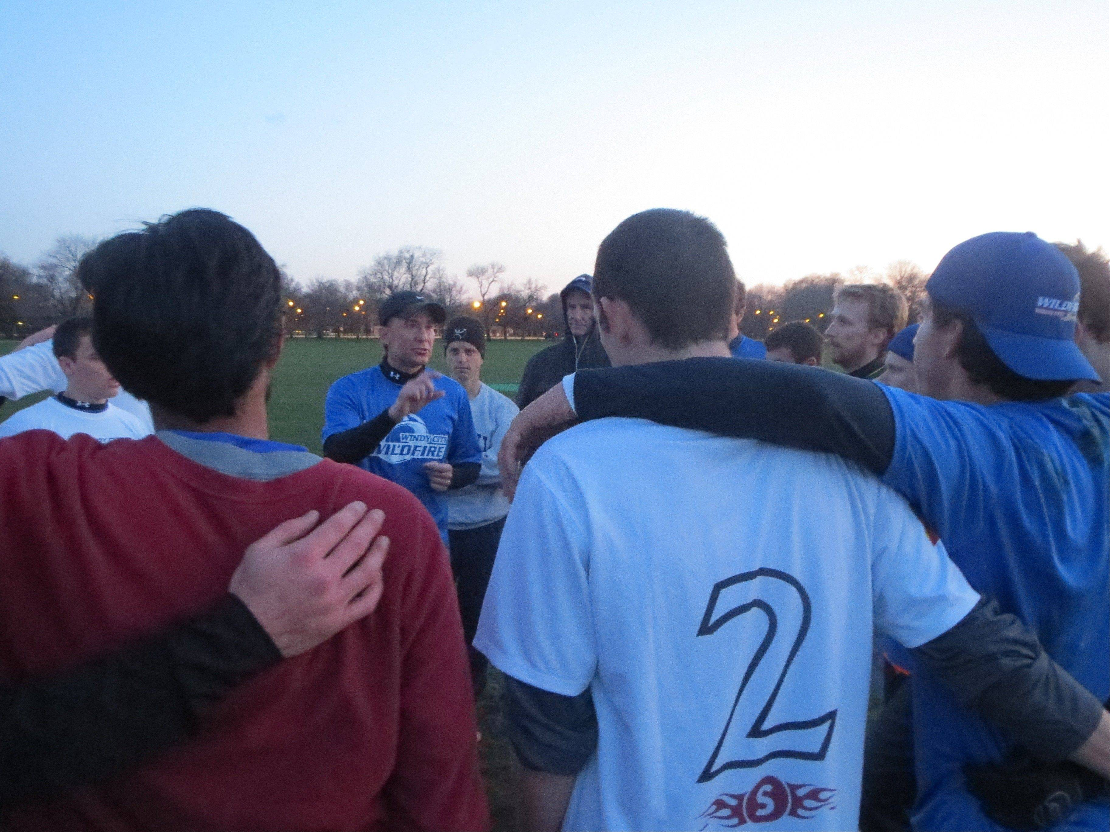 Reviewing points about the value of making good cuts in the game of Ultimate, head coach John Hock of Naperville (wearing hat in center) addresses players on the Windy City Wildfire, Chicago's newest professional sports franchise.