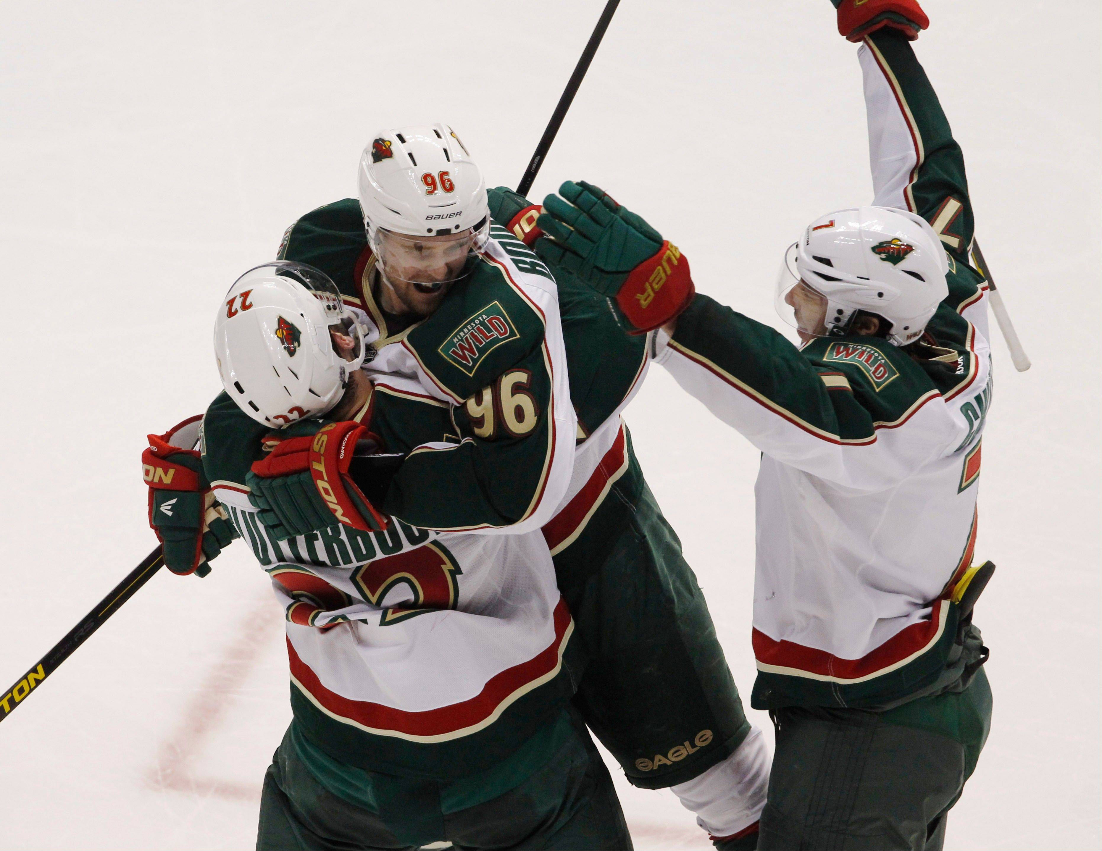 Minnesota left wing Pierre-Marc Bouchard, center, celebrates after his open-net goal with right wing Cal Clutterbuck, left, and center Matt Cullen late in the third period of the Wild's 3-1 victory over Colorado on Saturday. The Wild will face the Blackhawks in the opening round of the NHL playoffs.