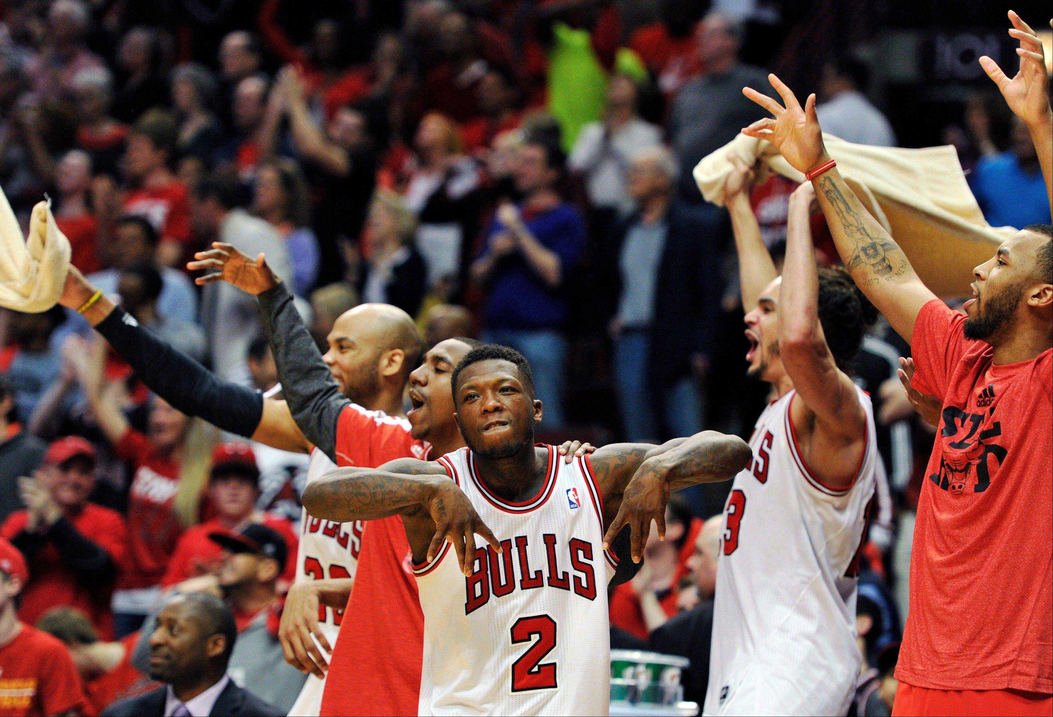 The Chicago Bulls bench including Nate Robinson (2) and Joakim Noah, center right, celebrates a basket against the Brooklyn Nets during the third overtime in Game 4 of their first-round NBA basketball playoff series Saturday, April 27, 2013, in Chicago. The Bulls won 142-134 in three overtimes.