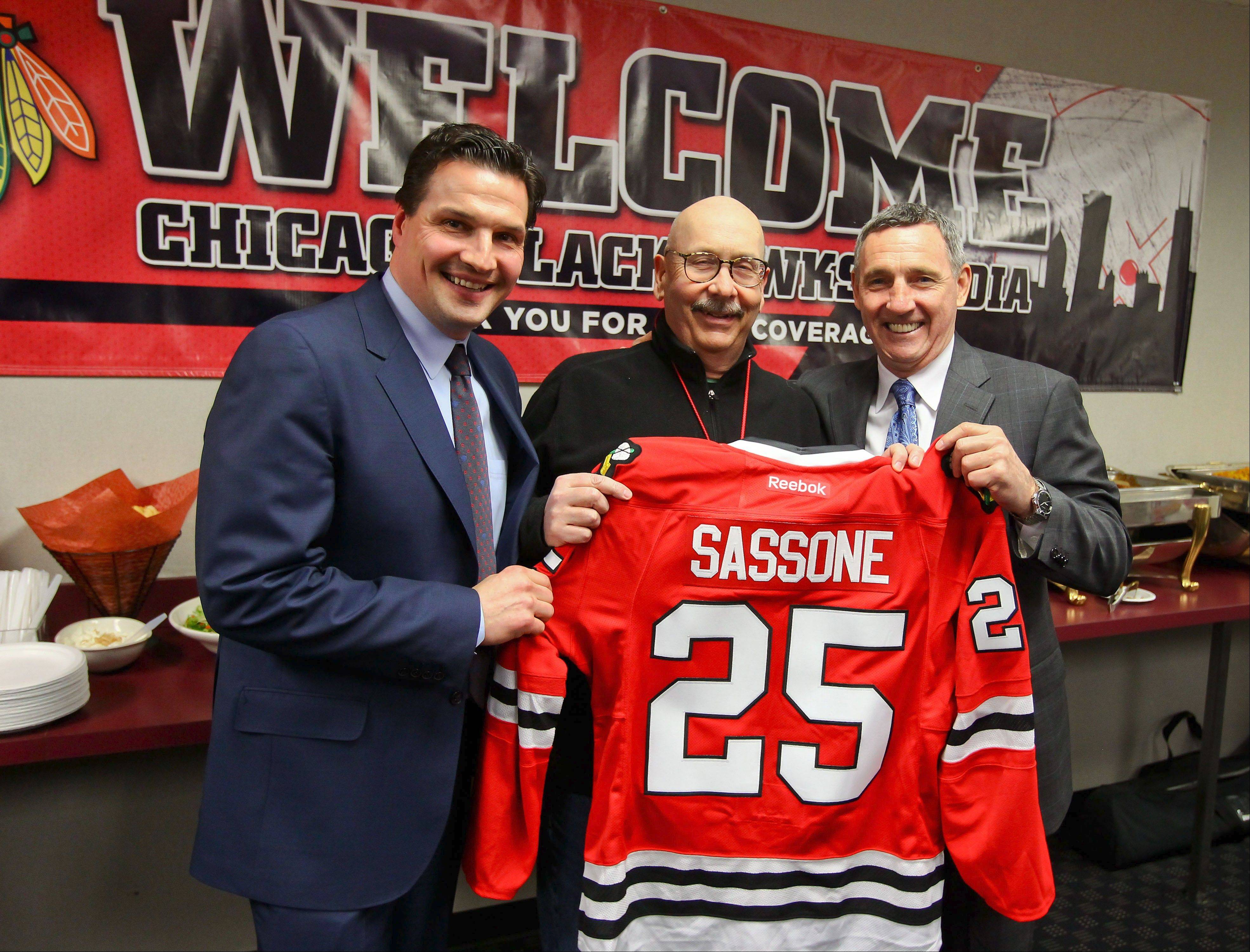 In honor of his 25 years of covering the team, Tim Sassone of the Daily Herald was presented with a Blackhawks jersey by broadcaster Eddie Olczyk, left, and hockey legend Denis Savard during Friday's home game.