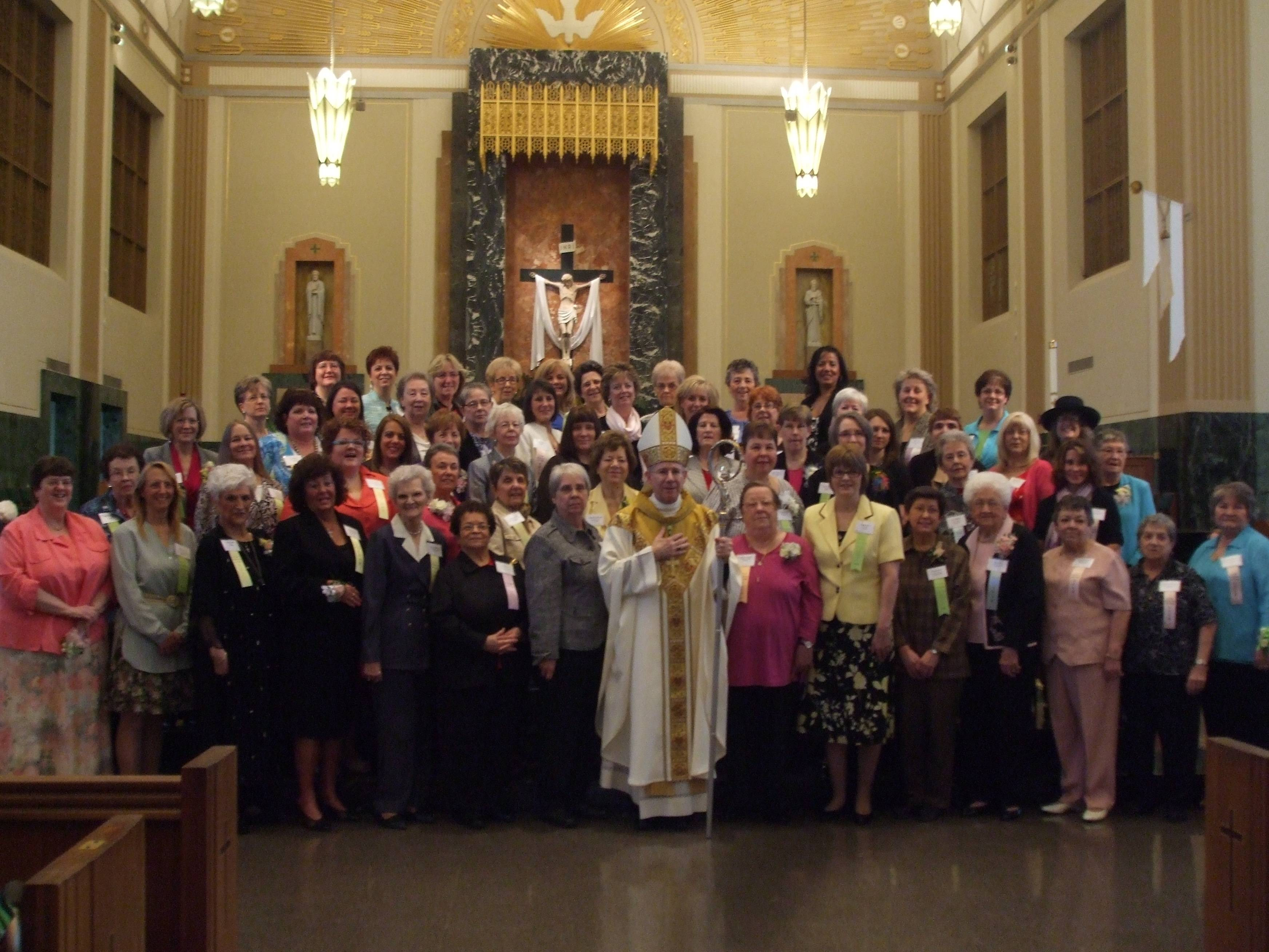 The ladies honored at the Women of the year Mass pose with Bishop Conlon on the altar at St. Raymond's Cathedral.