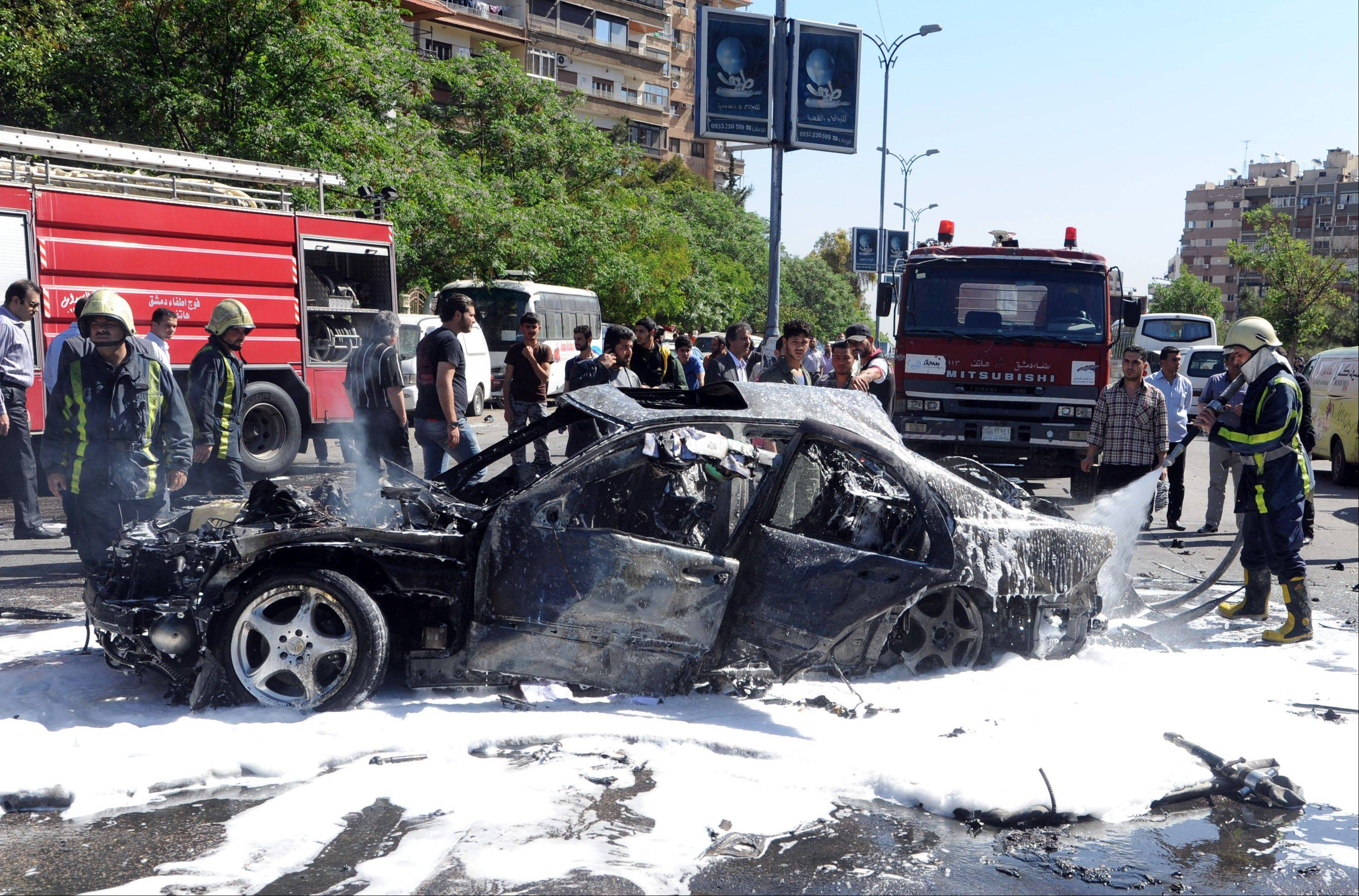Syrian firefighters extinguish burning cars after a car bomb exploded in the capital�s western neighborhood of Mazzeh, in Damascus, Syria, Monday. State-run Syrian TV says the country�s Prime Minister Wael al-Halqi has escaped an assassination attempt when a bomb went off near his convoy.