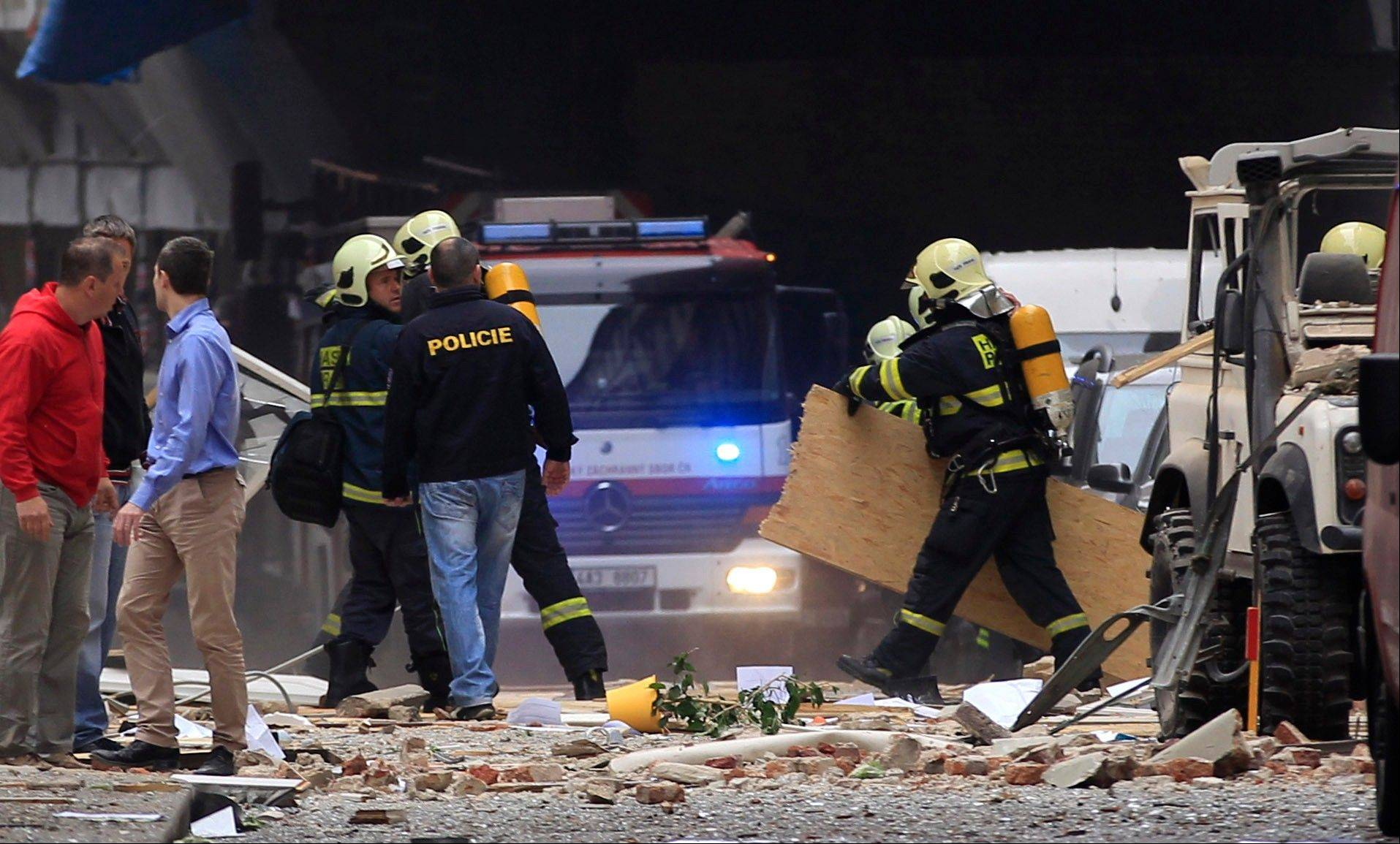 Policemen and firefighters inspect the scene of an explosion in downtown Prague, Czech Republic, Monday. Police said a powerful explosion has damaged a building in the center of the Czech capital, and they believe some people are buried in the rubble.
