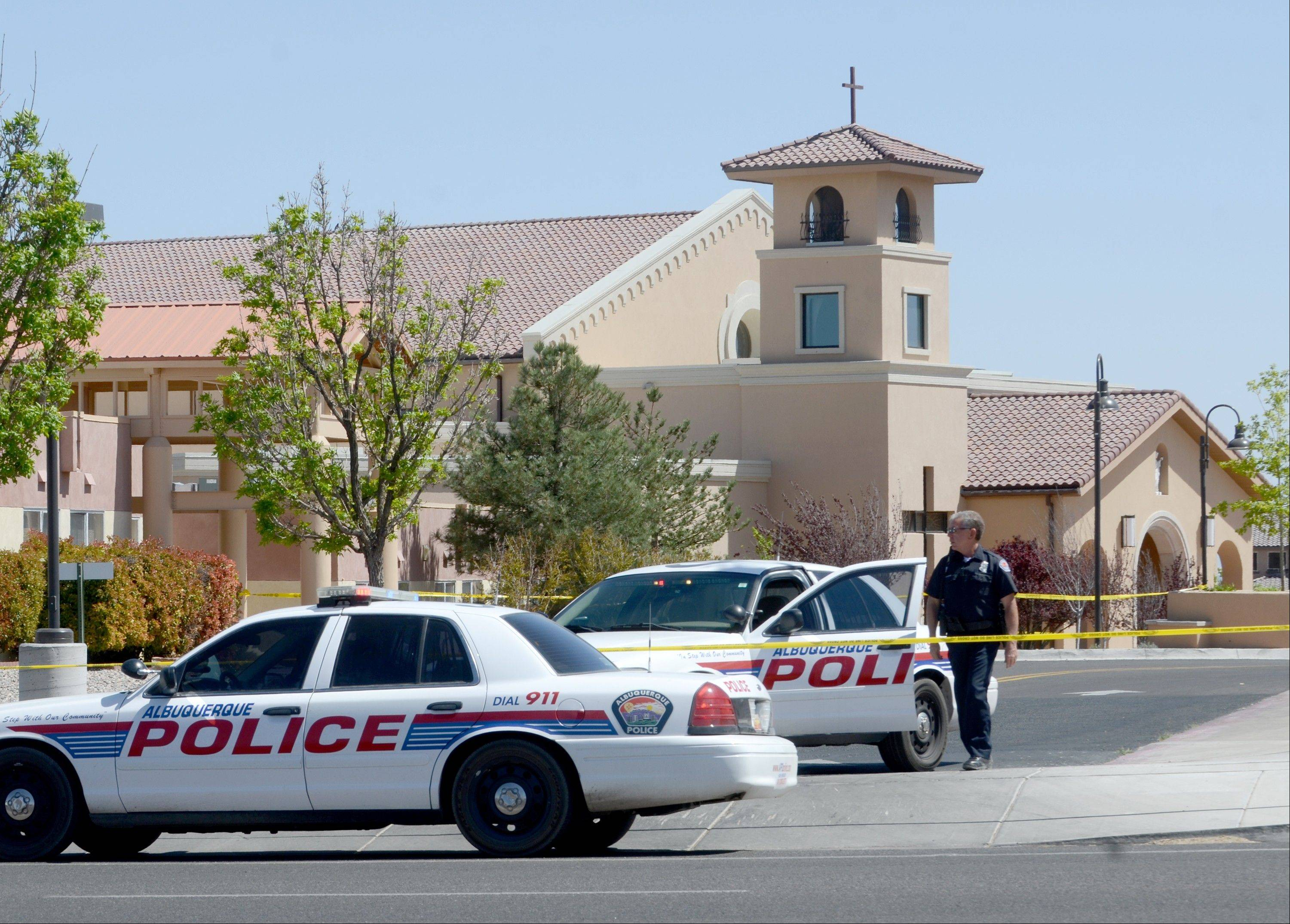 An Albuquerque Police officer walks behind the tape at St. Jude Thaddeus Catholic Church Sunday in Albuquerque, N.M., the scene of a multiple stabbing at the conclusion of morning services. Police say a 24-year-old man stabbed four people at a Catholic church in Albuquerque as a Sunday mass was nearing its end. Police spokesman Robert Gibbs says Lawrence Capener jumped over several pews at church around noon Sunday and walked up to the choir area where he began his attack.