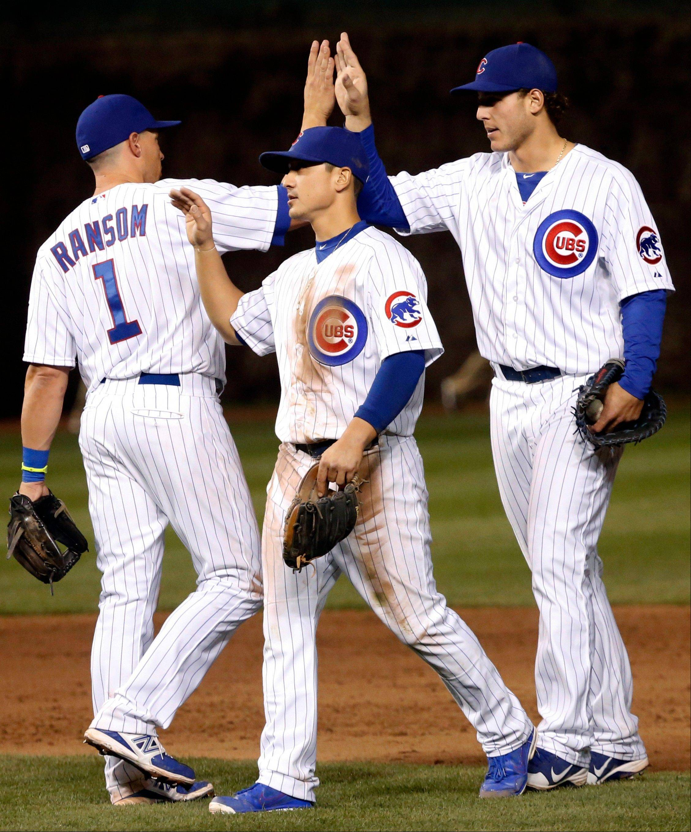 From left, Chicago Cubs third baseman Cody Ransom, second baseman Darwin Barney and first baseman Anthony Rizzo celebrate their 5-3 win over the San Diego Padres after a baseball game, Monday, April 29, 2013, in Chicago.