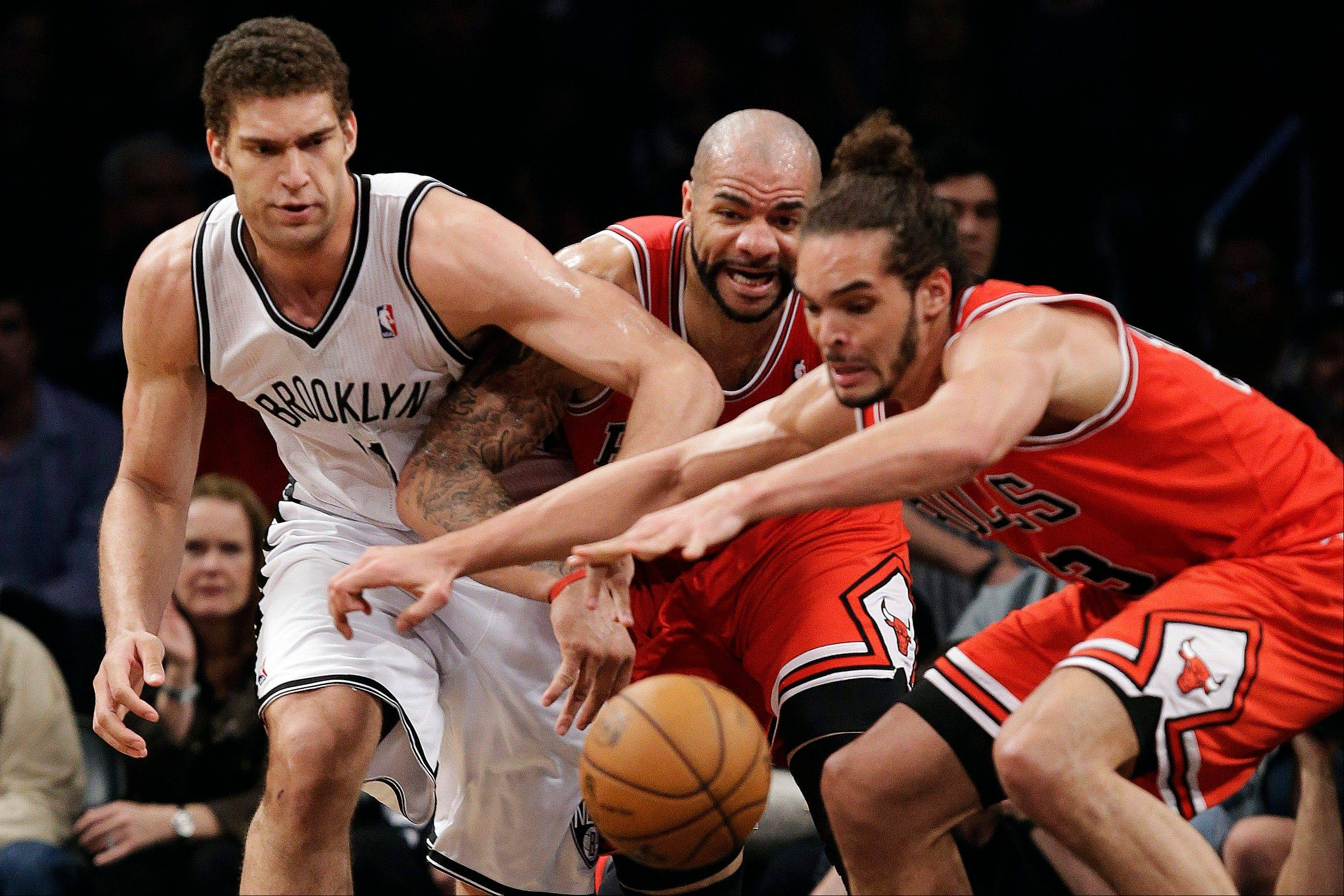 Brooklyn Nets center Brook Lopez (11), Chicago Bulls forward Carlos Boozer, center, and center Joakim Noah, right, compete for a loose ball in the first half of Game 5 of their first-round NBA basketball playoff series Monday in New York.