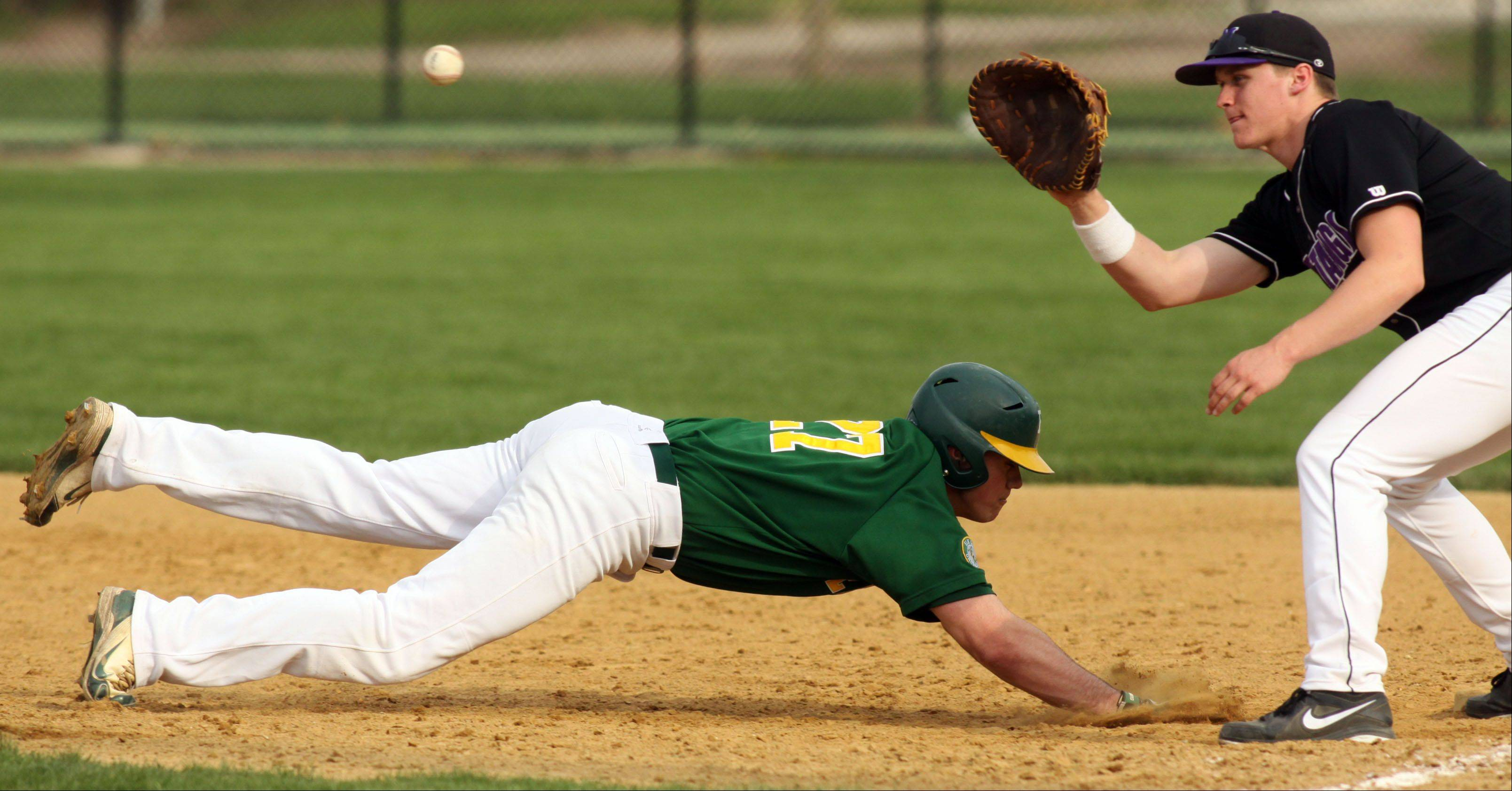 Rolling Meadows first baseman Erik Schurtz, right, fields the pick-off throw as Elk Grove?s Mikey Maize slides safely back to the bag at South Salk Park in Rolling Meadows on Monday evening.