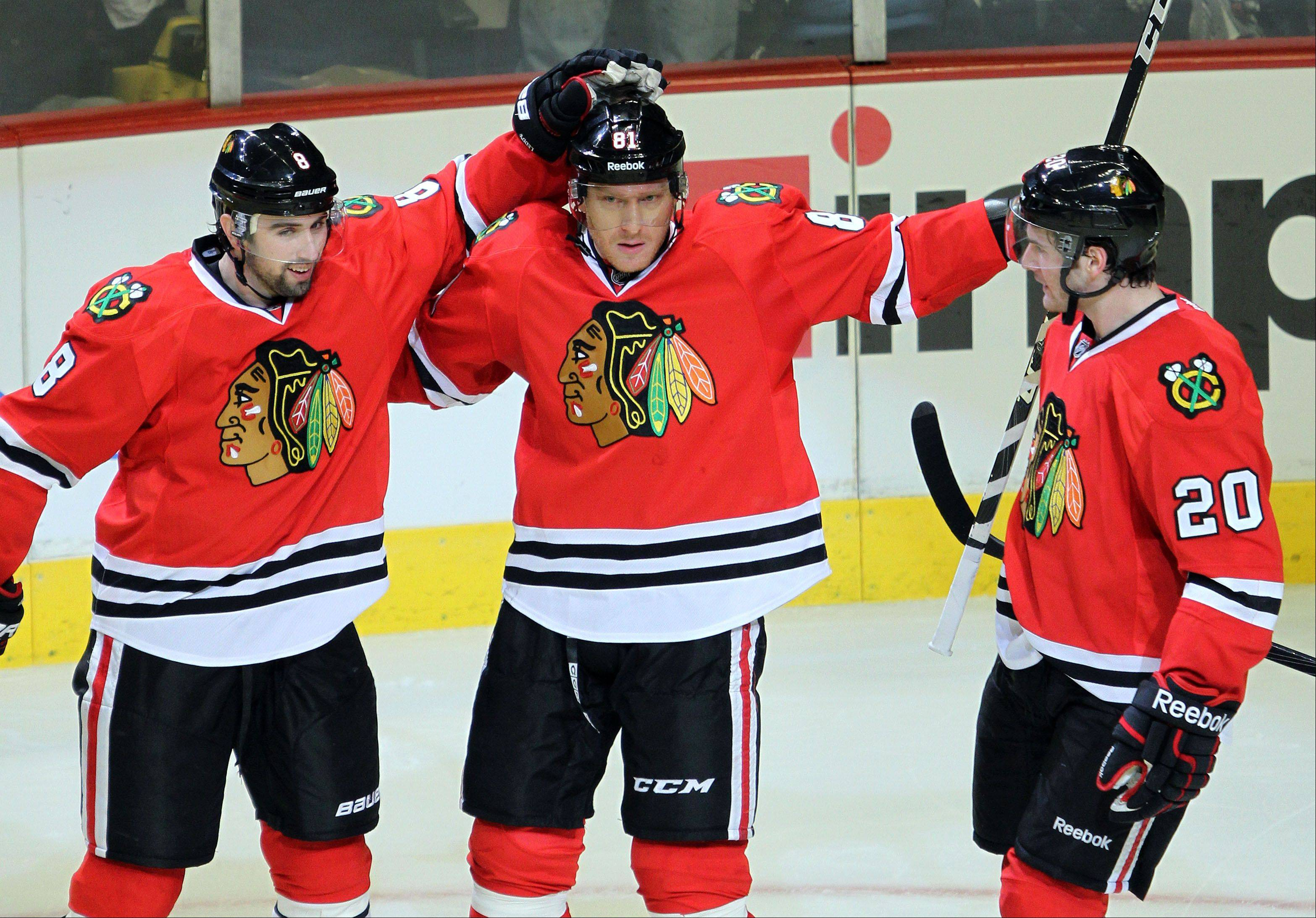 Blackhawks defenseman Nick Leddy and left wing Brandon Saad celebrate with right wing Marian Hossa after his 2nd period goal during their game Sunday night at the United Center in Chicago.