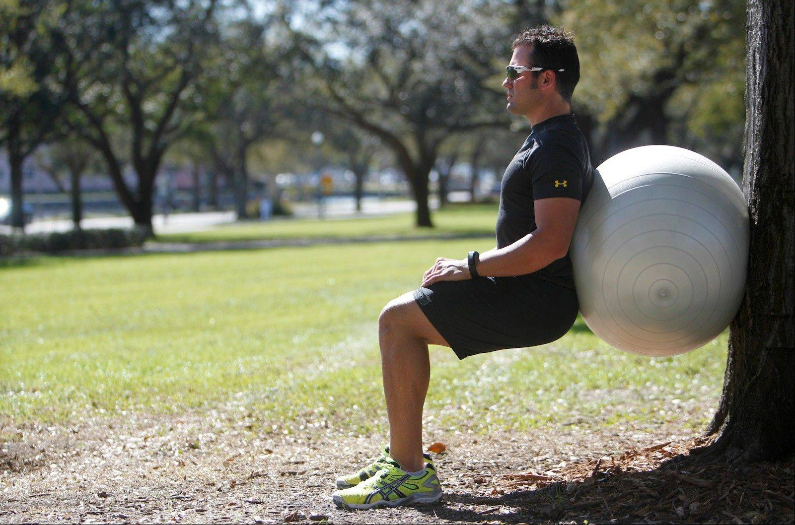 A wall squat with ball strengthens the lower body.