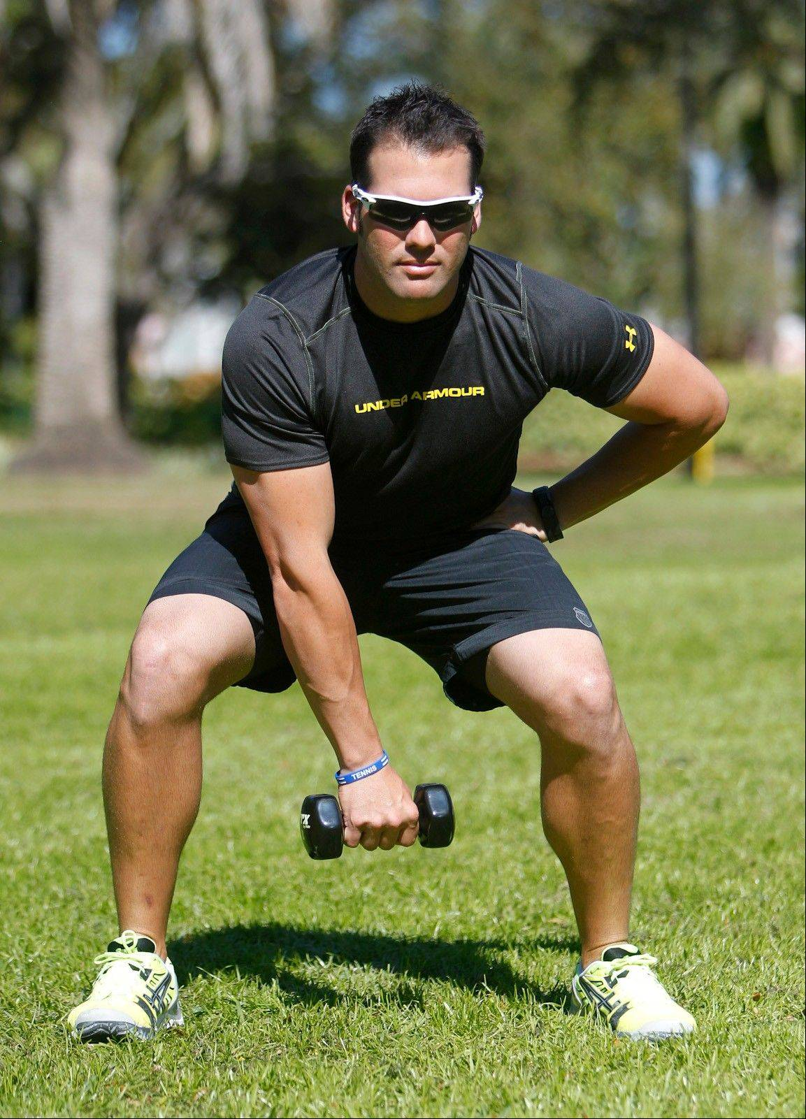 A squat and single-arm swing works the thighs, hips, glutes, back, arms, shoulders and core.