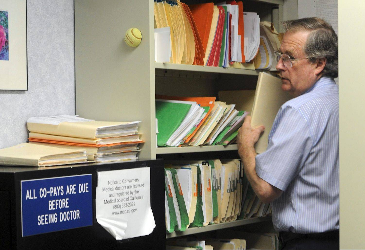 Dr. Ted Hole files papers, answers calls, makes appointments and checks in his patients among other duties.