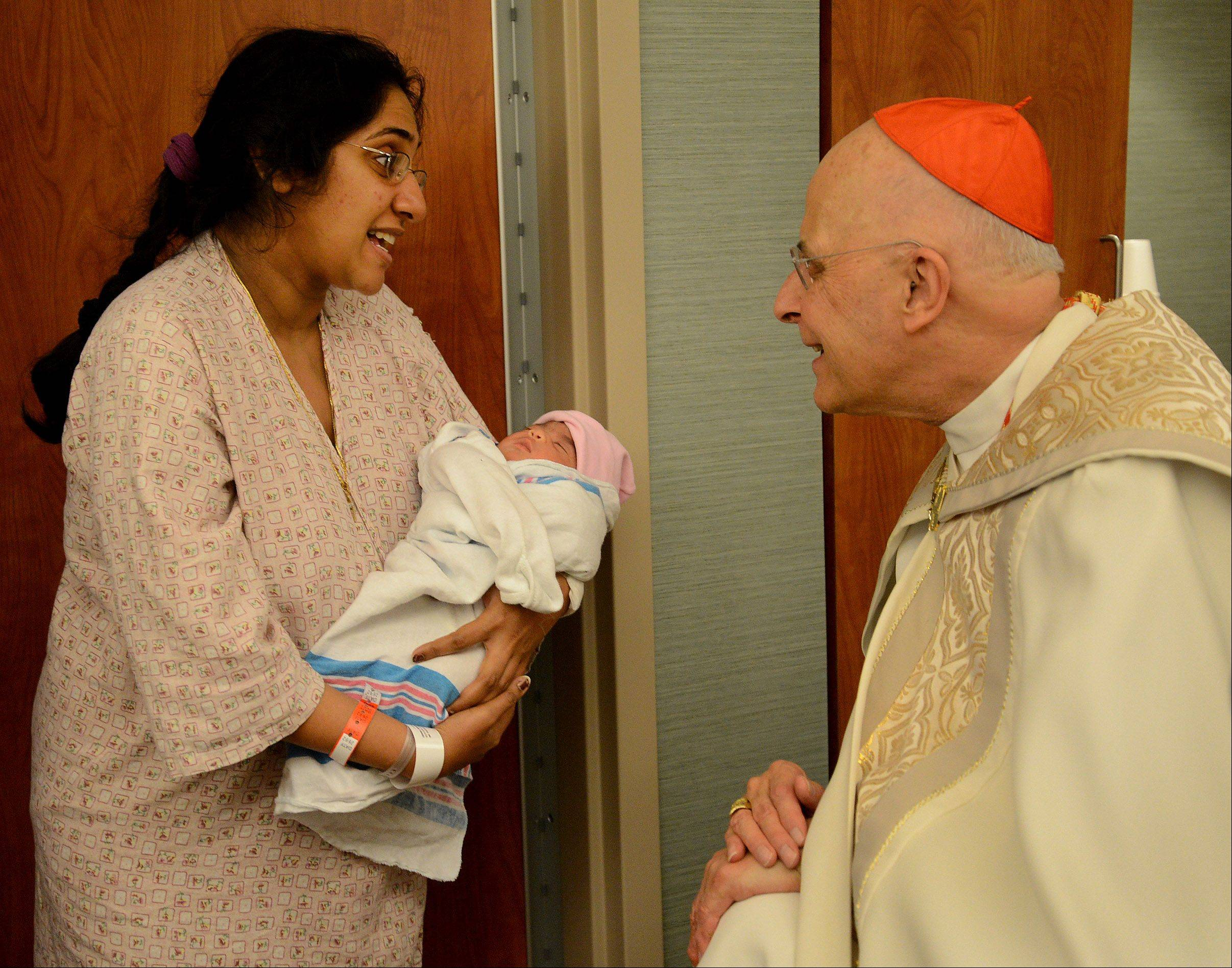 Cardinal Francis George stops and chats with Shereena Cheeran of Elgin and her newborn, Norelle. George blessed the staff, patients and families of the new Alexian Brothers Women and Children's Hospital in Hoffman Estates on Monday.