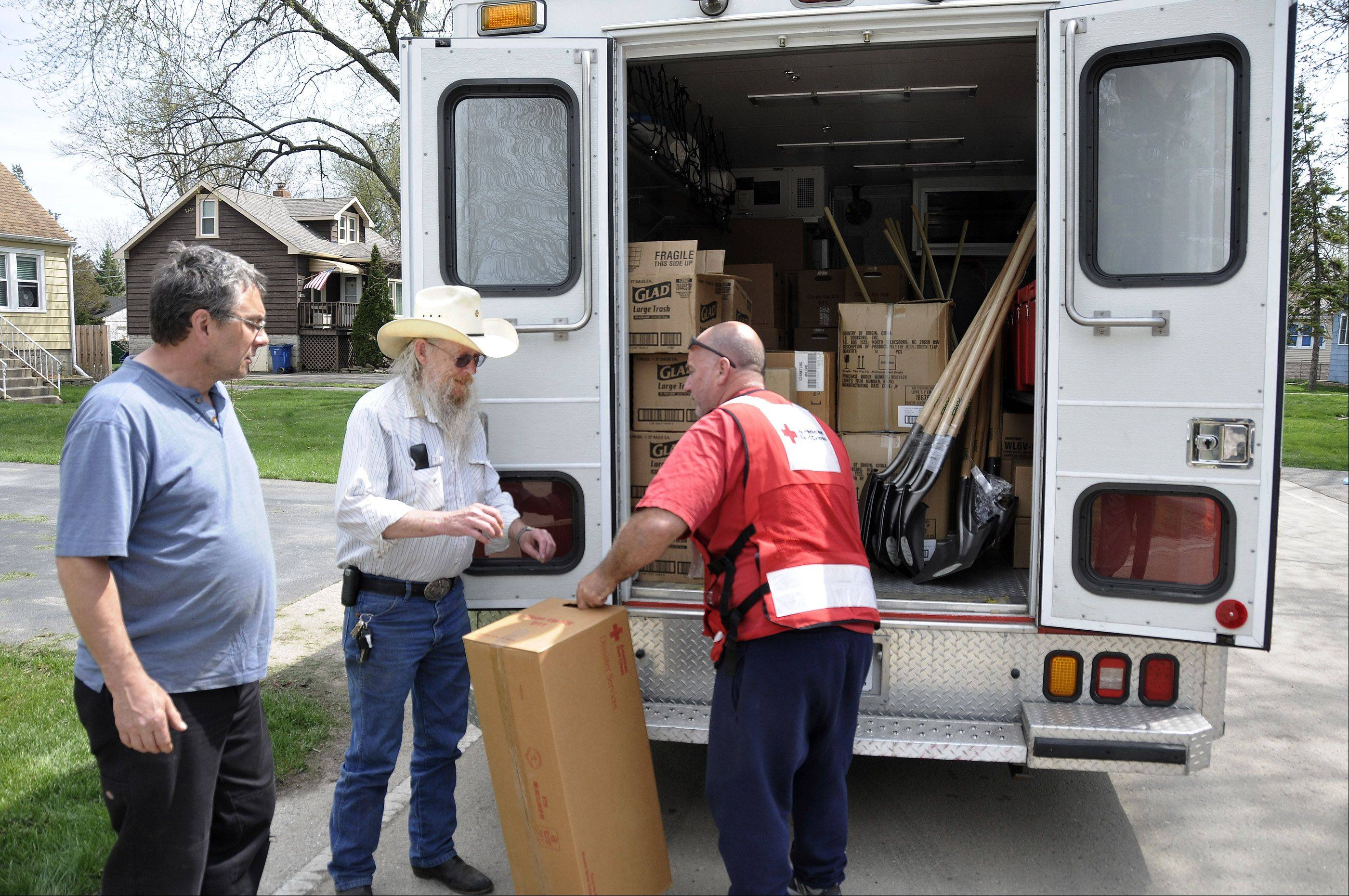 Lisle residents Terry Griffitt, left, and Joe Delaney, center, get cleaning supplies from Red Cross driver Mike Roselli on McKinley Avenue.