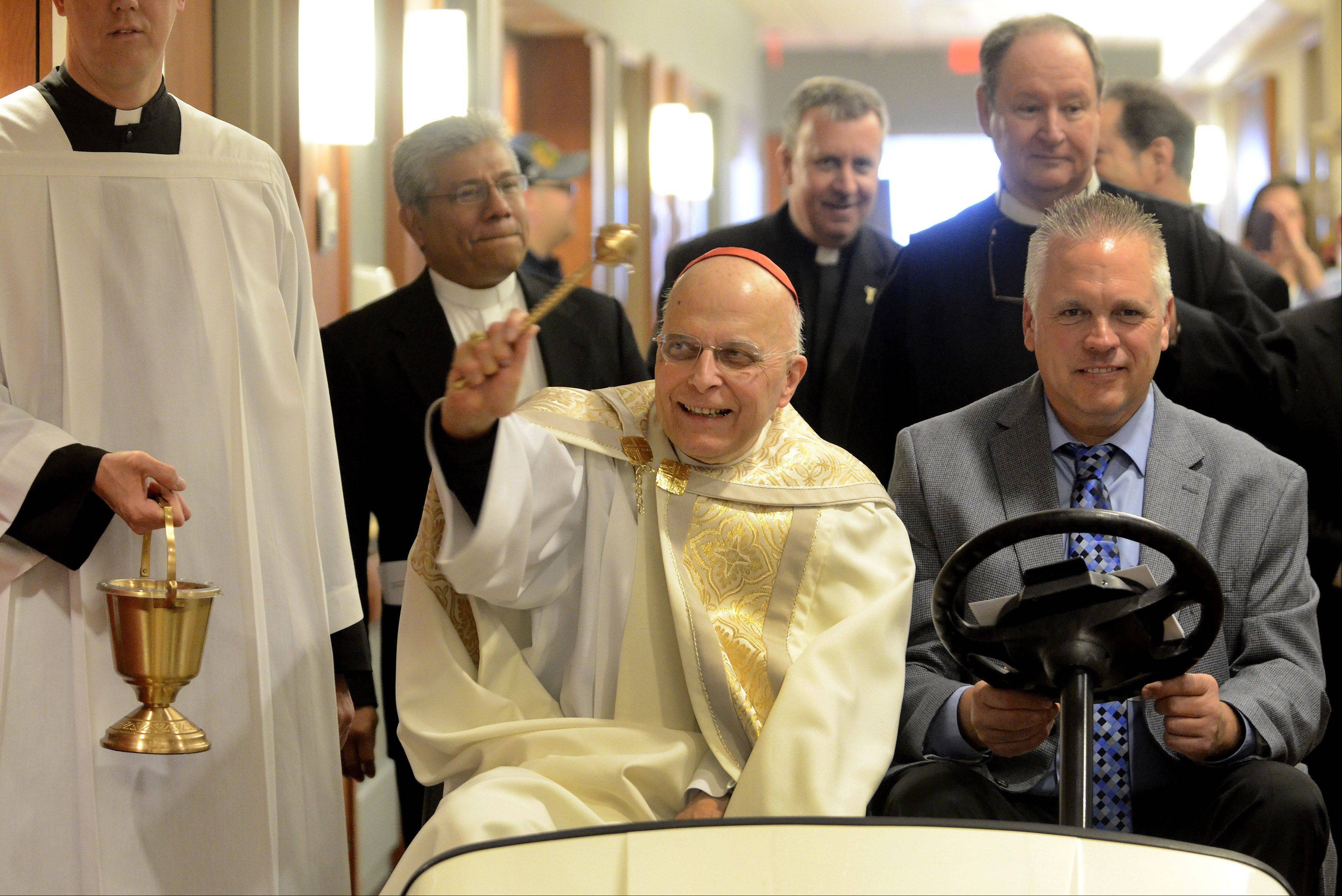 Cardinal Francis George rides through the hallways of the new Alexian Brothers Women & Children's Hospital in Hoffman Estates on Monday, blessing the staff, patients and families.