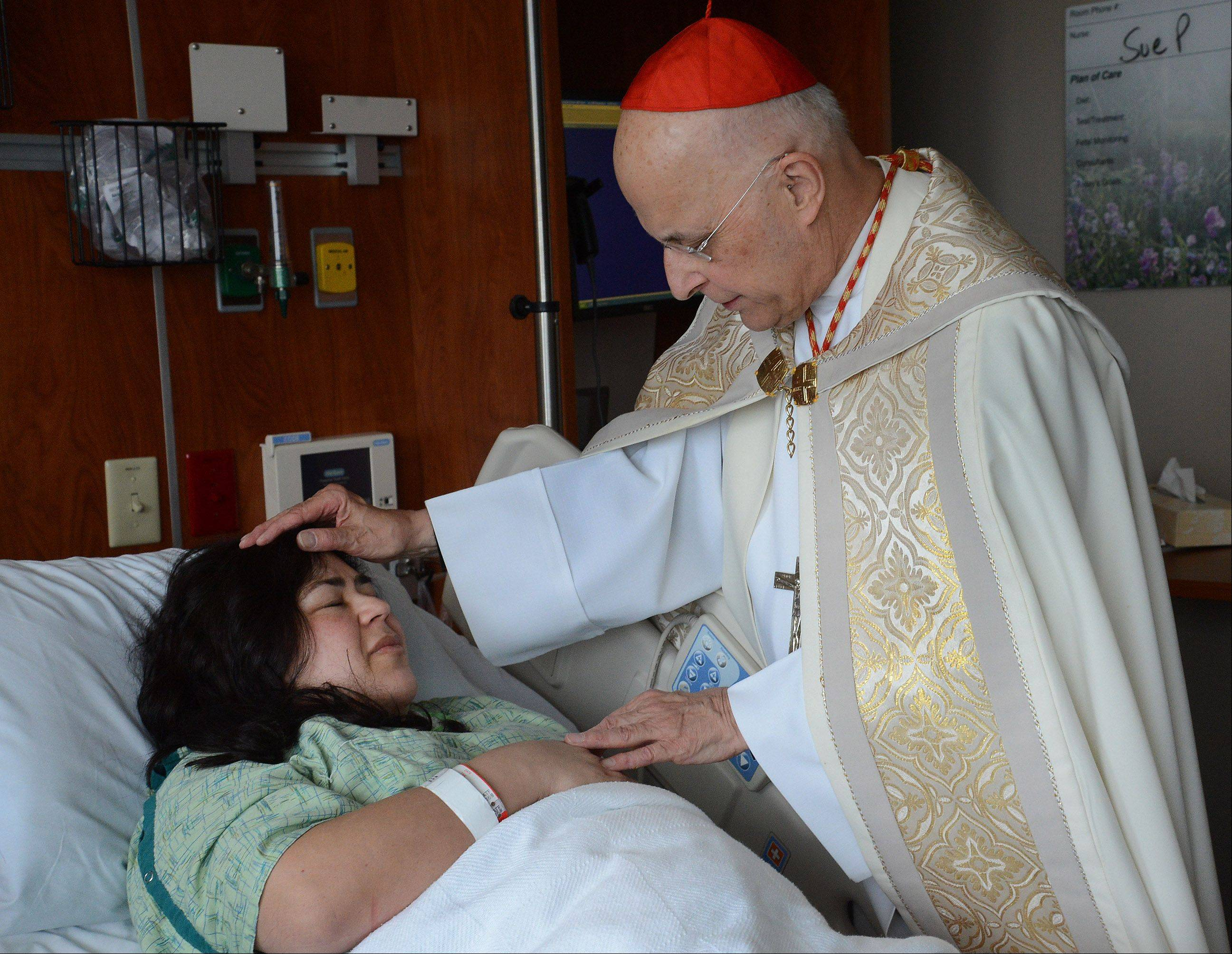 Cardinal Francis George gives a blessing to Maria Mora of Carpentersville at the new Alexian Brothers Women & Children's Hospital in Hoffman Estates. George visited the hospital Monday for the first time.