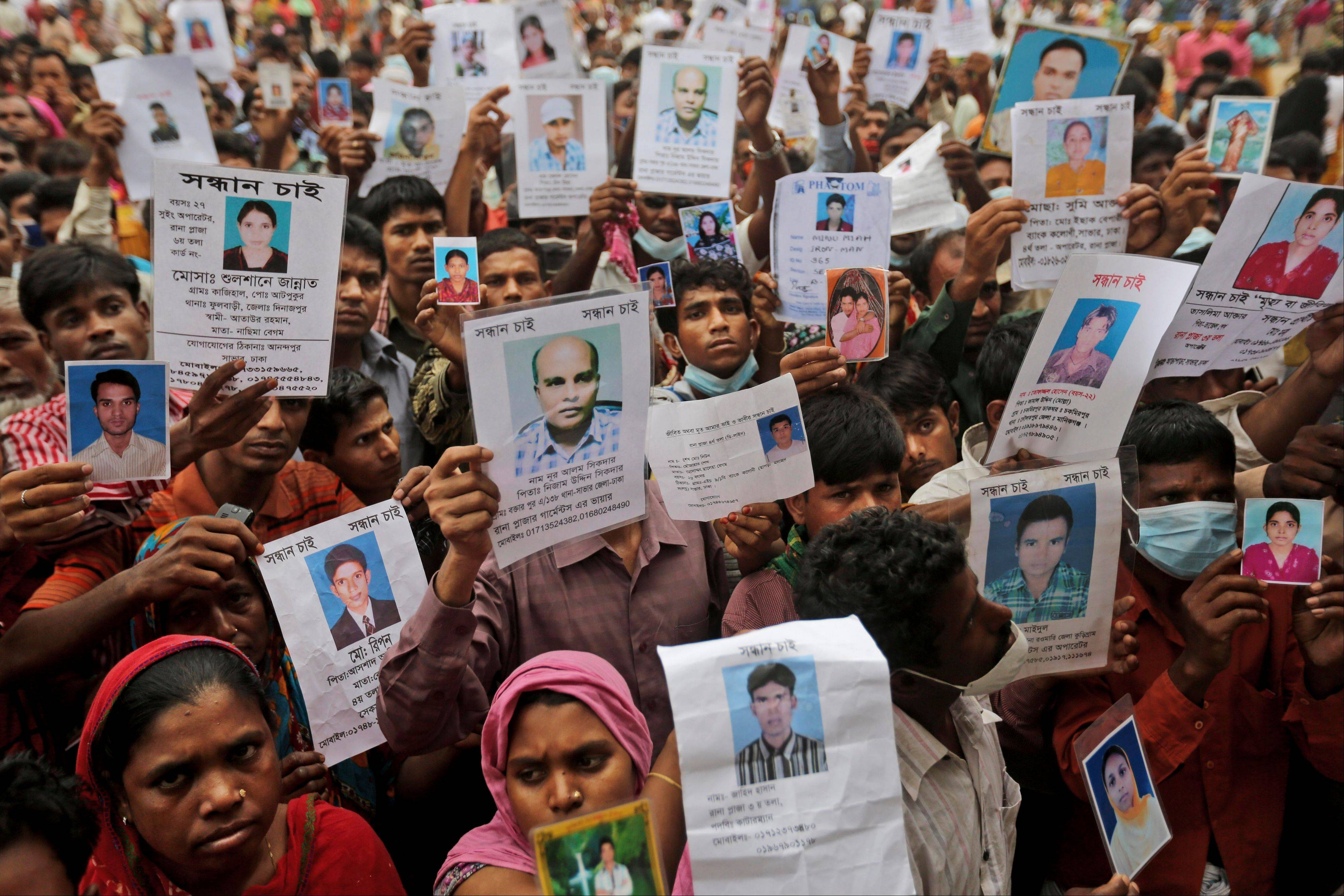 Bangladeshi relatives of missing workers in a building that collapsed Wednesday hold pictures of their family members in Savar, near Dhaka, Bangladesh, Sunday.