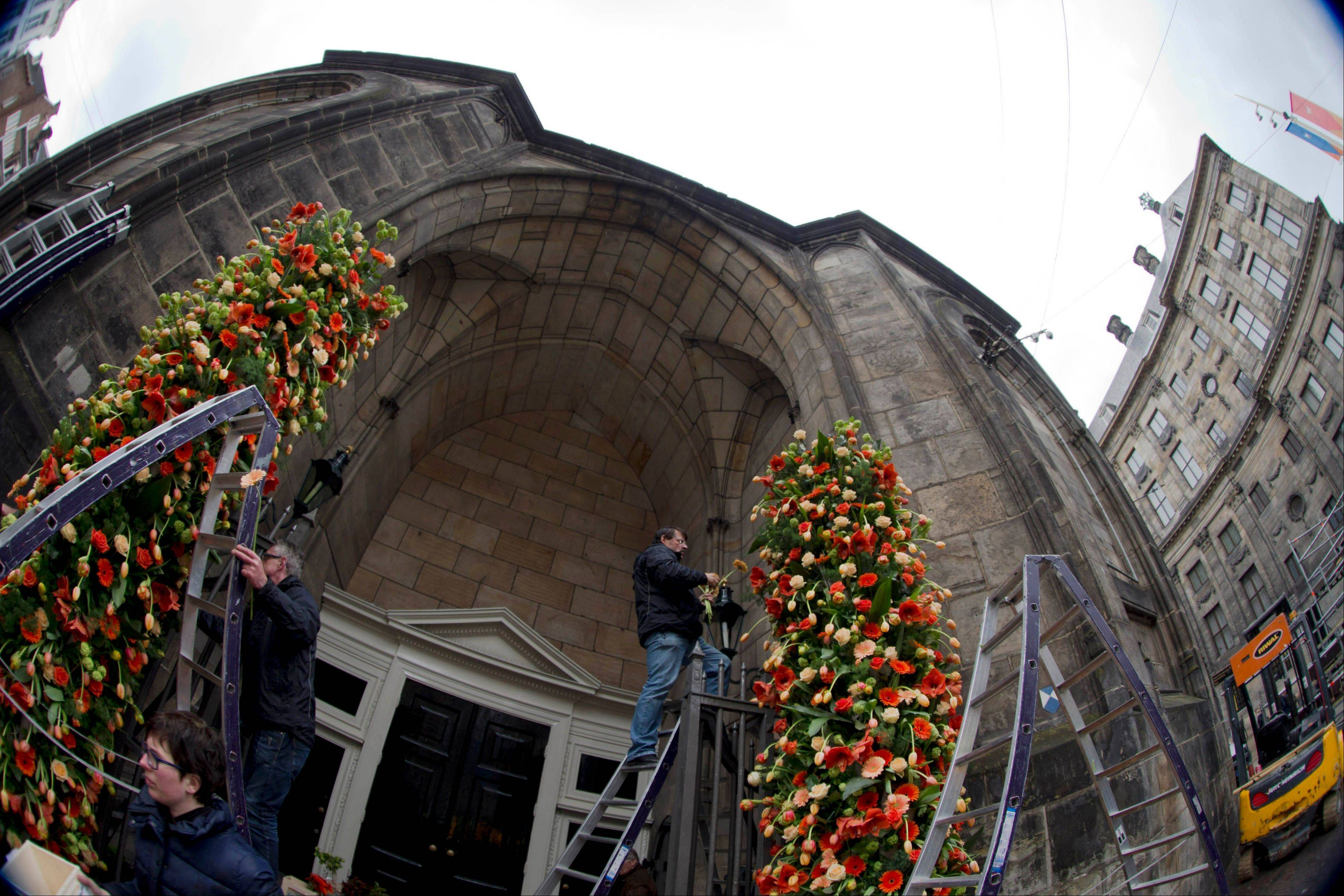 Floral arrangements decorate the entrance of Nieuwe Kerk, adjacent to the Royal Palace, right, in Amsterdam, Netherlands, Monday as officials prepare for a once-in-a-generation rotation of royal titles.