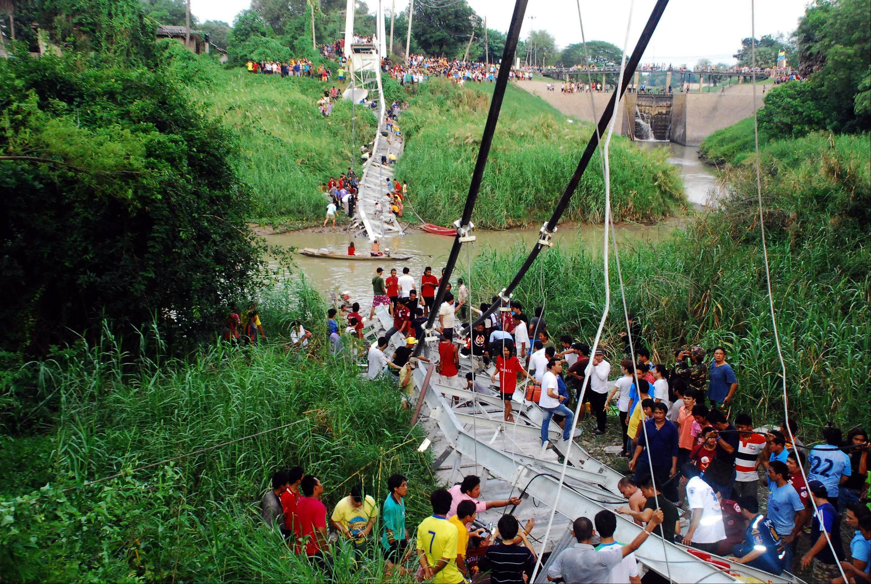Thai villagers and rescuers sift through the wreckage of a suspension bridge crossing the Pasak river after it collapsed Sunday in Ayutthaya province, central Thailand. Police say at least four people have been killed and a dozen have been injured when the small bridge collapsed in the accident.