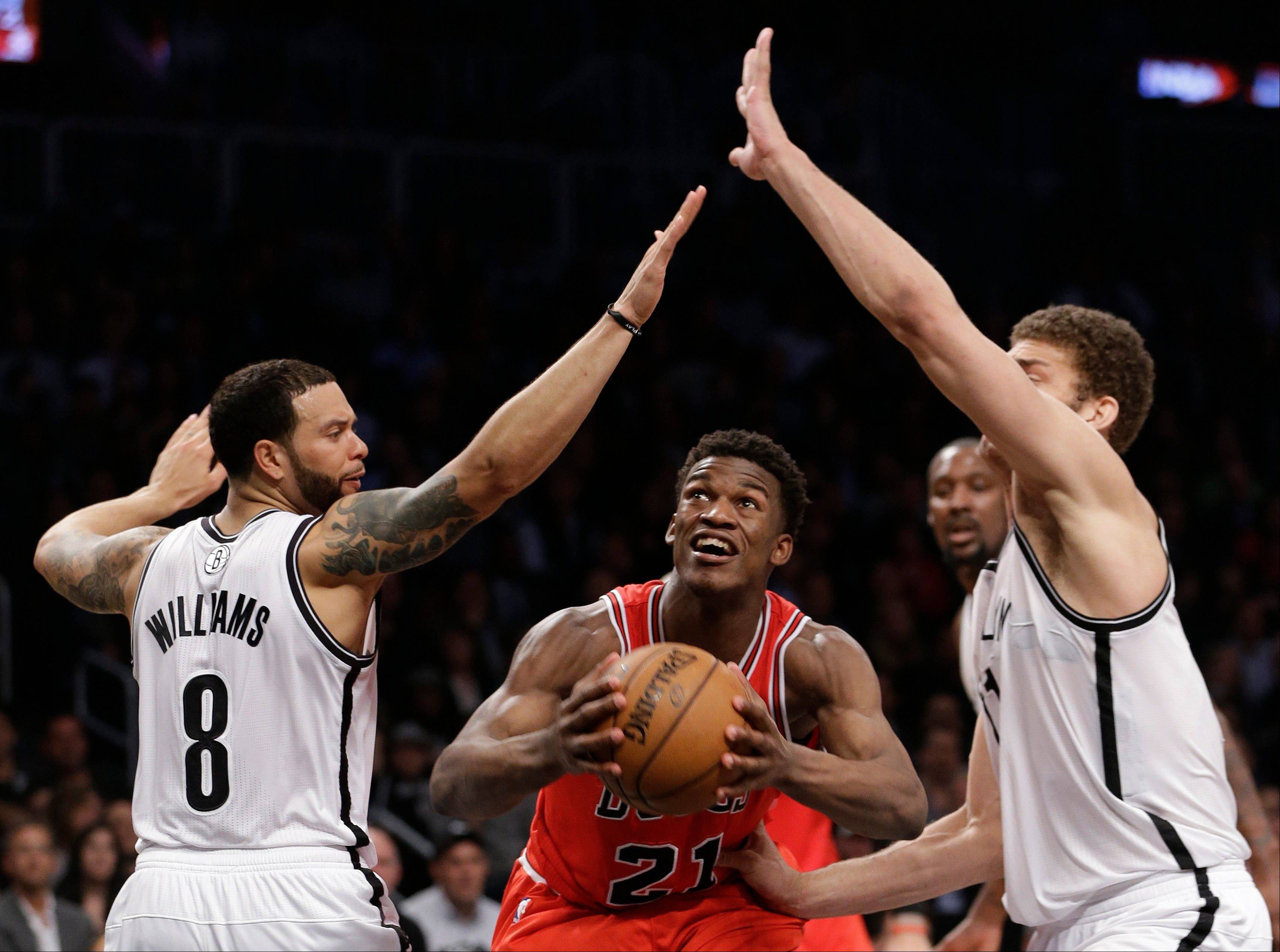Brooklyn Nets guard Deron Williams, left, and center Brook Lopez surround the Bulls' Jimmy Butler in the second half of Game 5 Monday night.