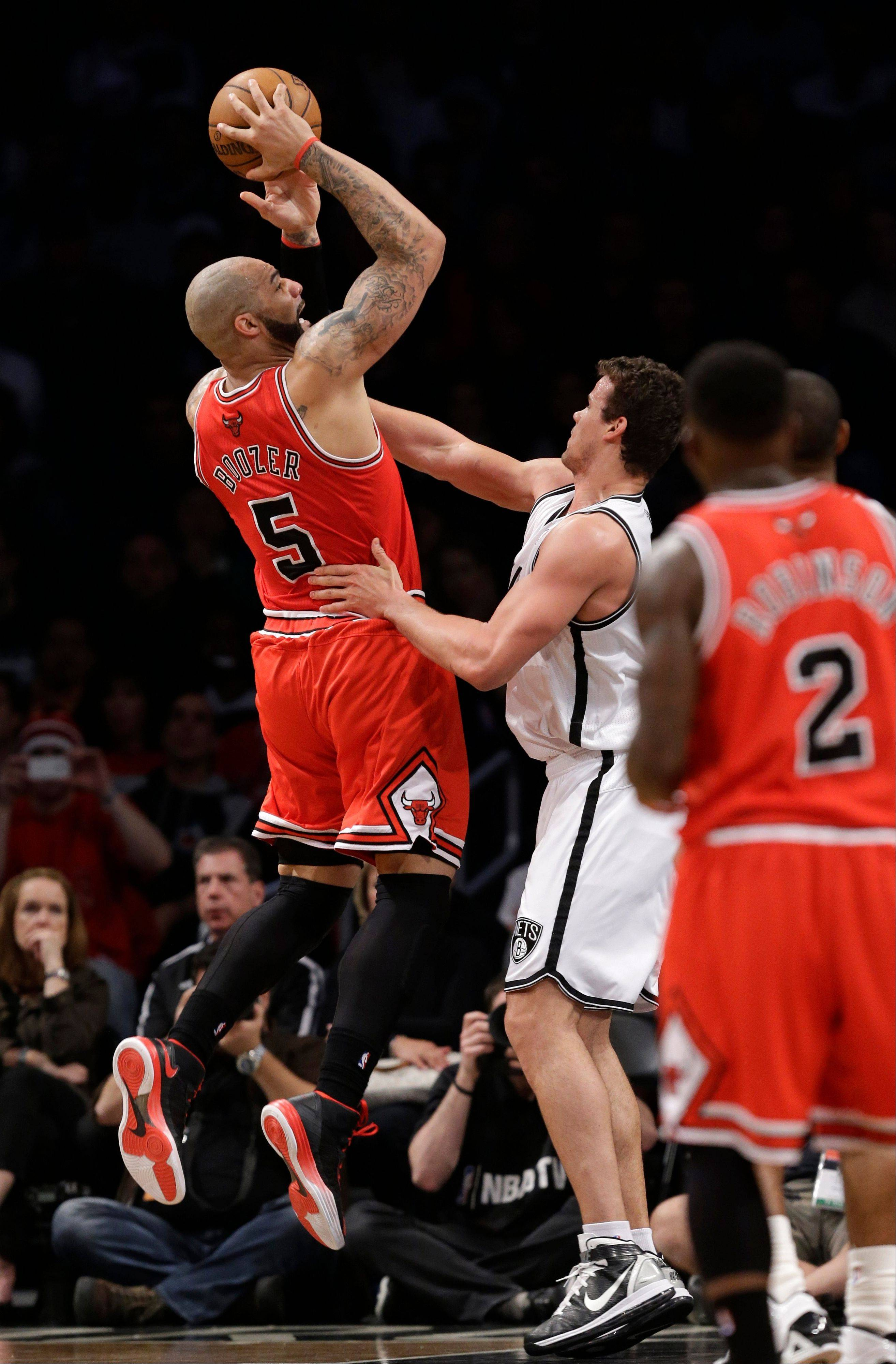Chicago Bulls forward Carlos Boozer (5) shoots over Brooklyn Nets forward Kris Humphries (43) in the first half of Game 5 of their first-round NBA basketball playoff series, Monday, April 29, 2013, in New York.