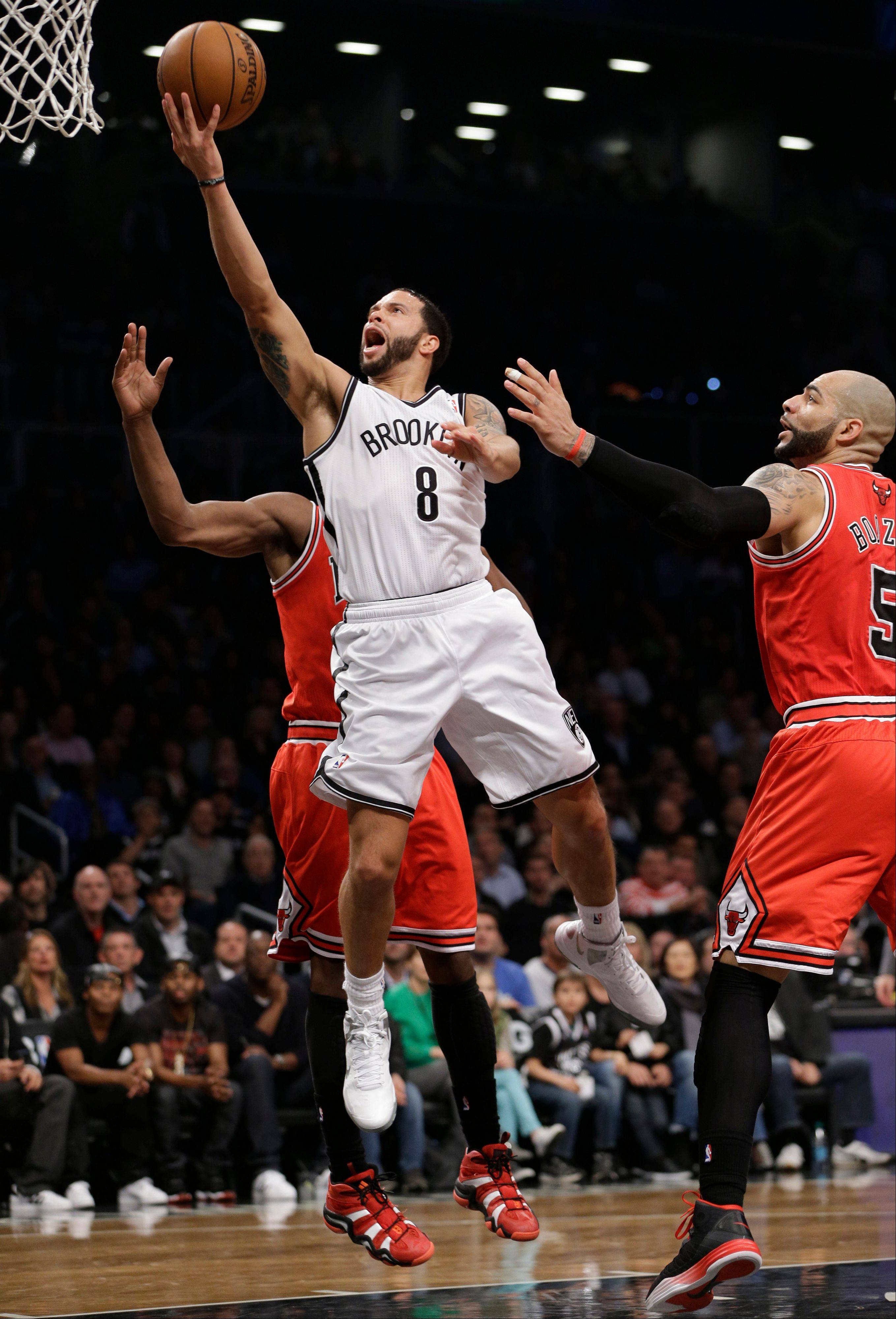 Brooklyn Nets guard Deron Williams (8) goes up for a layup past Chicago Bulls forward Carlos Boozer (5) in the first half of Game 5 of their first-round NBA basketball playoff series, Monday, April 29, 2013, in New York. The Nets won 110-91.