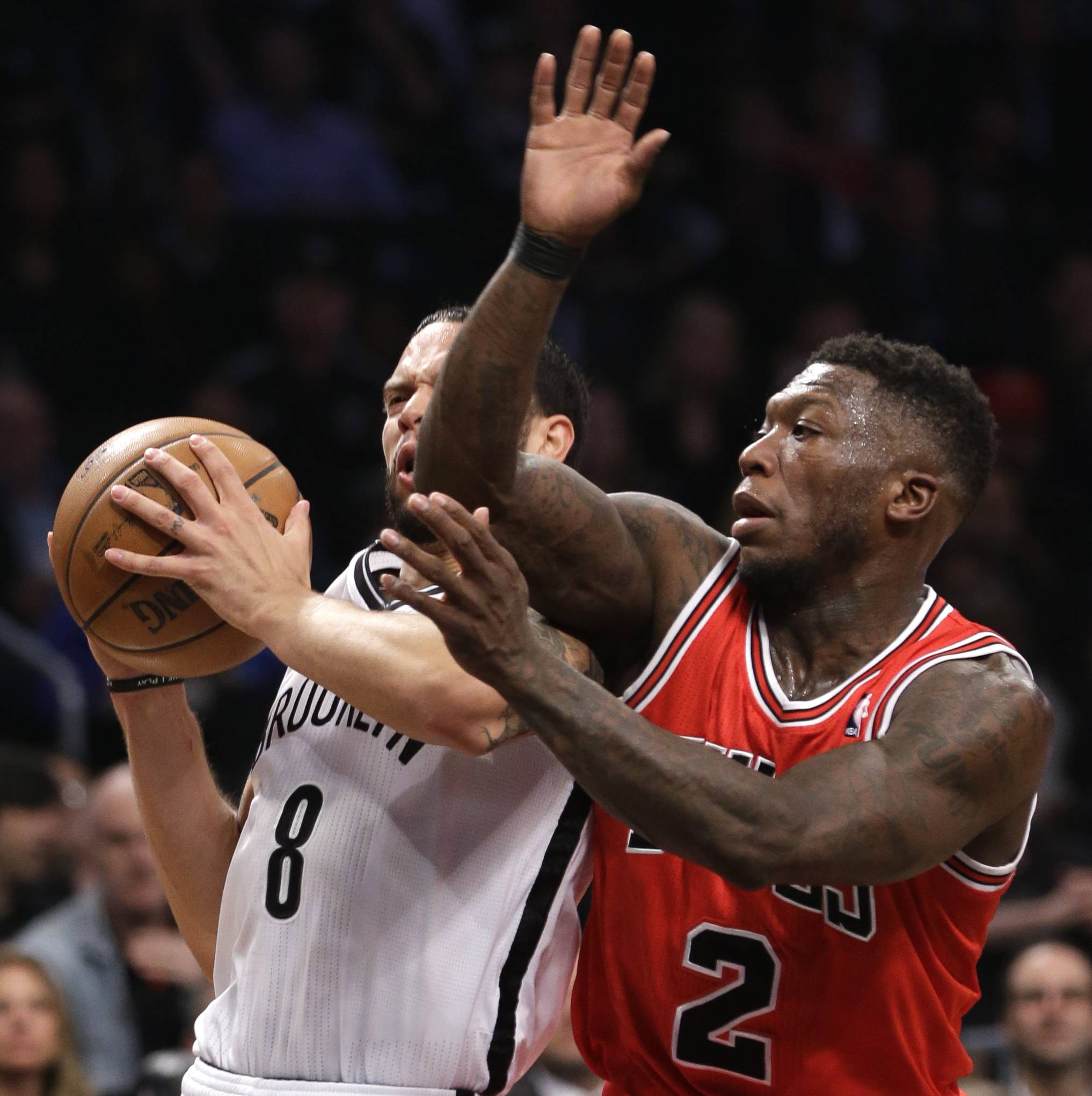 Brooklyn Nets guard Deron Williams (8) collides with Chicago Bulls guard Nate Robinson (2) as he drives toward the basket in the first half of Game 5 of their first-round NBA basketball playoff series, Monday, April 29, 2013, in New York.