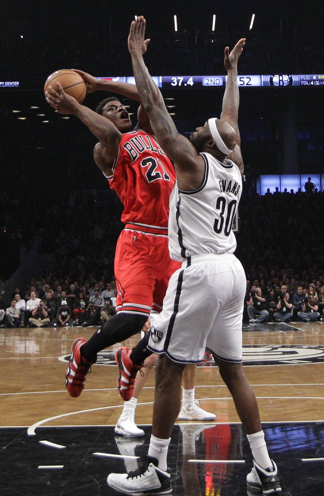 Chicago Bulls forward Jimmy Butler (21) looks to shoot around Brooklyn Nets forward Reggie Evans (30) in the second half of Game 5 of their first-round NBA basketball playoff series, Monday, April 29, 2013, in New York. The Nets won 110-91.