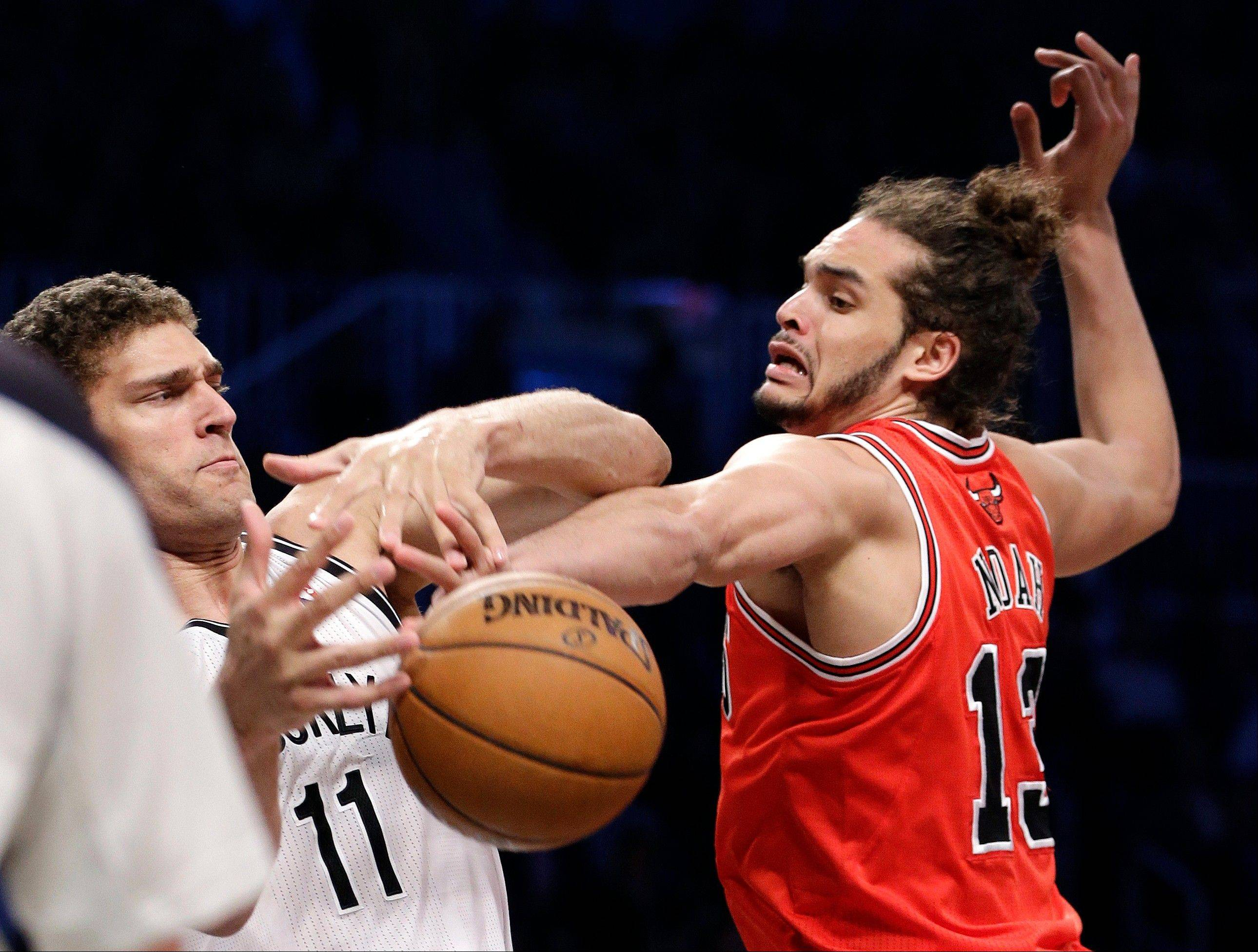 Chicago Bulls center Joakim Noah (13) steals the ball from Brooklyn Nets center Brook Lopez (11) in the first half of Game 5 of their first-round NBA basketball playoff series, Monday, April 29, 2013, in New York.