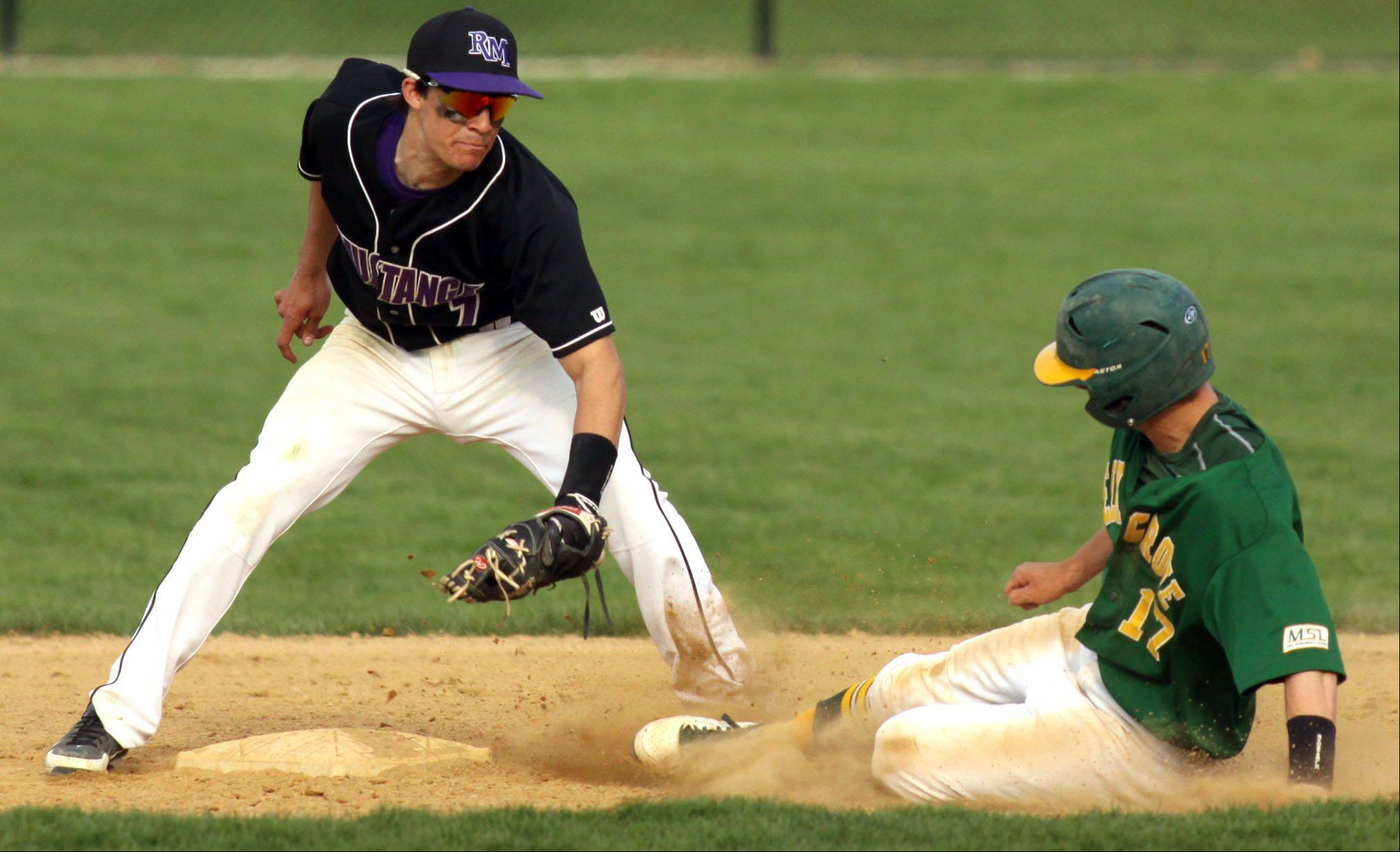 Rolling Meadows' Zach Schultz, left, prepares to tag out Elk Grove's Patrick O'Malley on a steal attempt at second base at South Salk Park in Rolling Meadows on Monday evening.