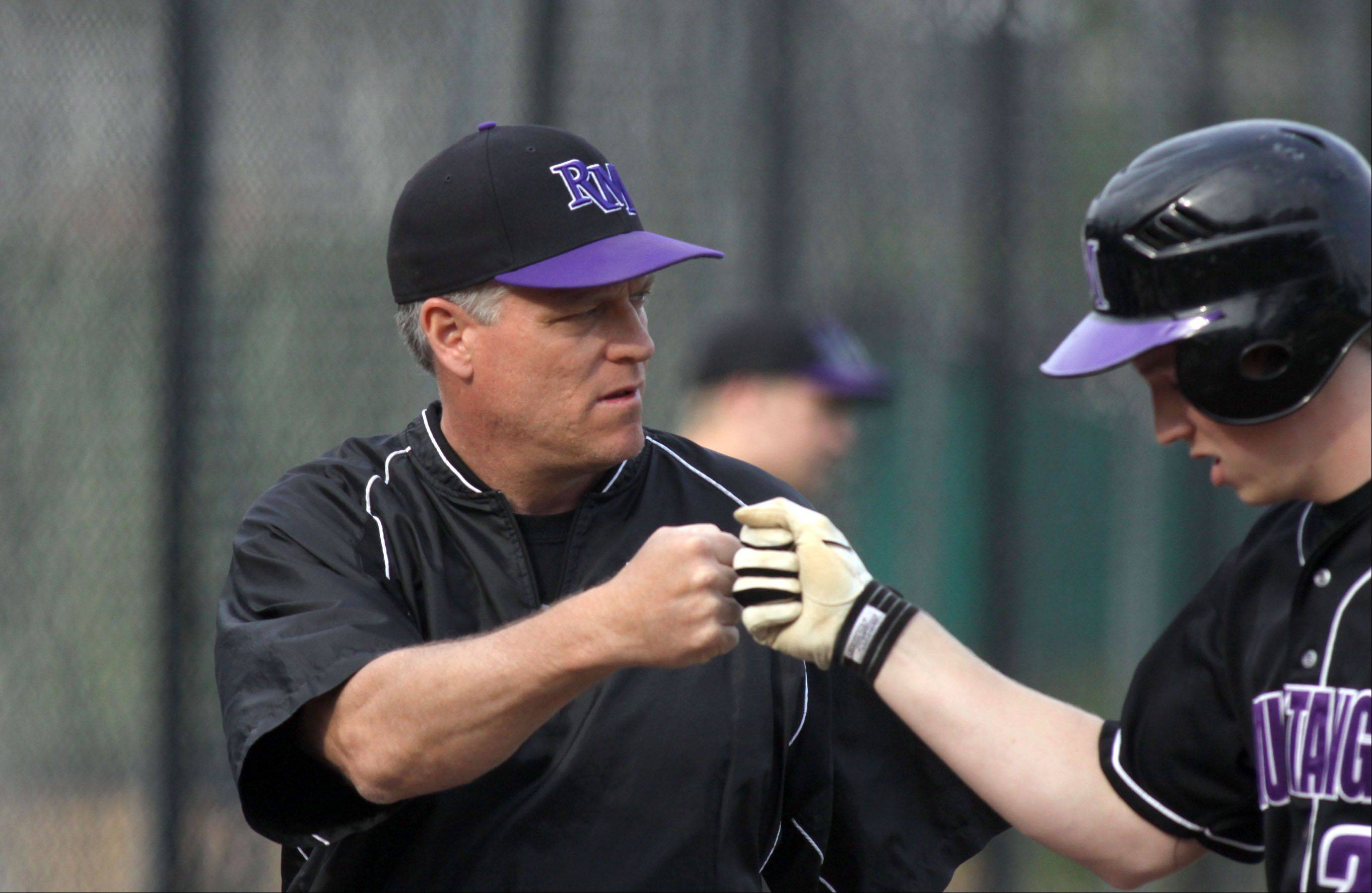 Rolling Meadows head coach and former big-leaguer Jim Lindeman, left, offers encouragement to Dan Hendricks against Elk Grove at South Salk Park in Rolling Meadows on Monday evening.