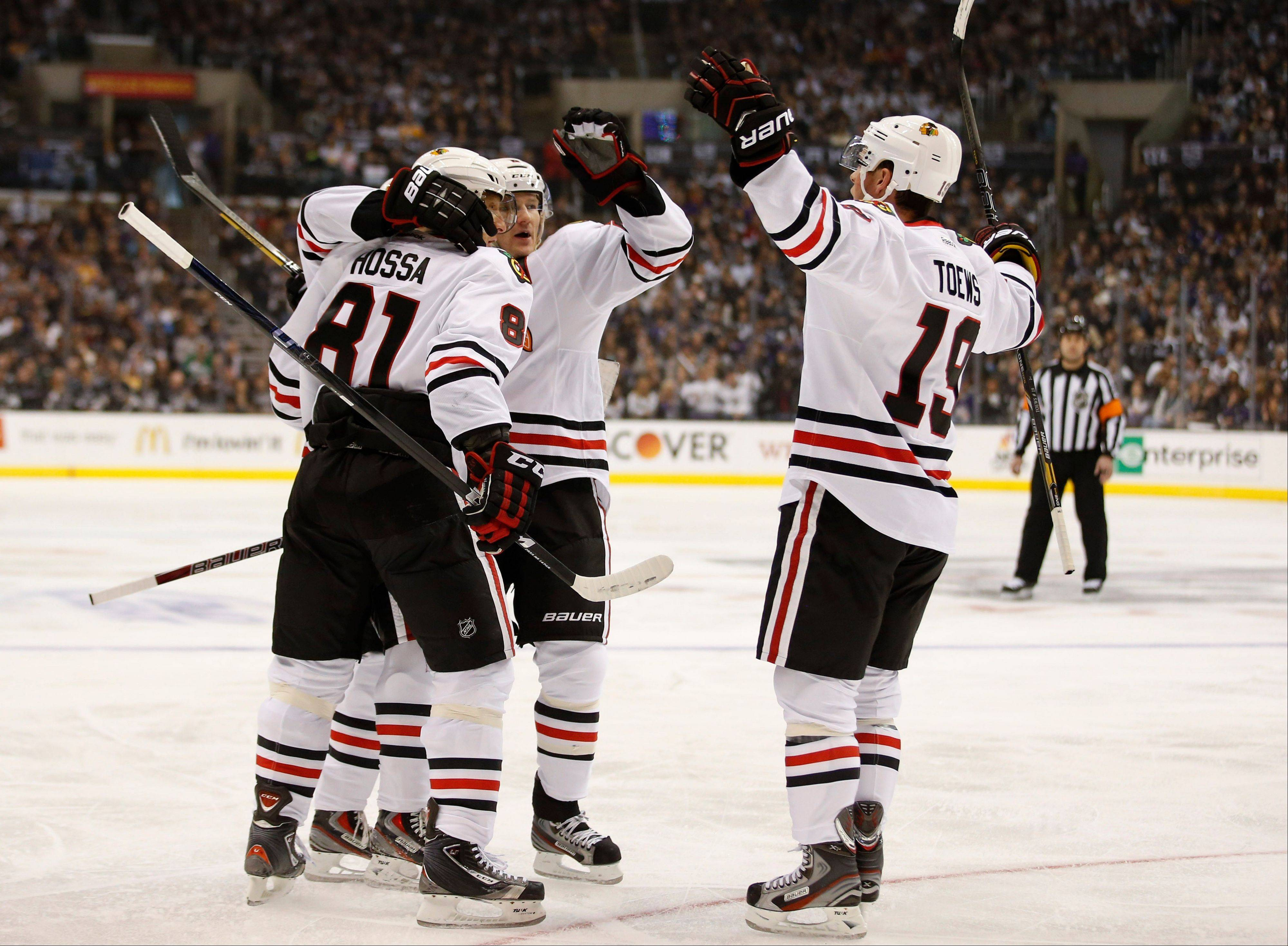 Blackhawks winger Marian Hossa (81), Patrick Kane, Duncan Keith, second from right, and Jonathan Toews celebrate a goal by Kane against the Los Angeles Kings in Los Angeles on Jan. 19. It was banner-raising night for the defending Stanley Cup champion Kings, and the Blackhawks won 5-2.