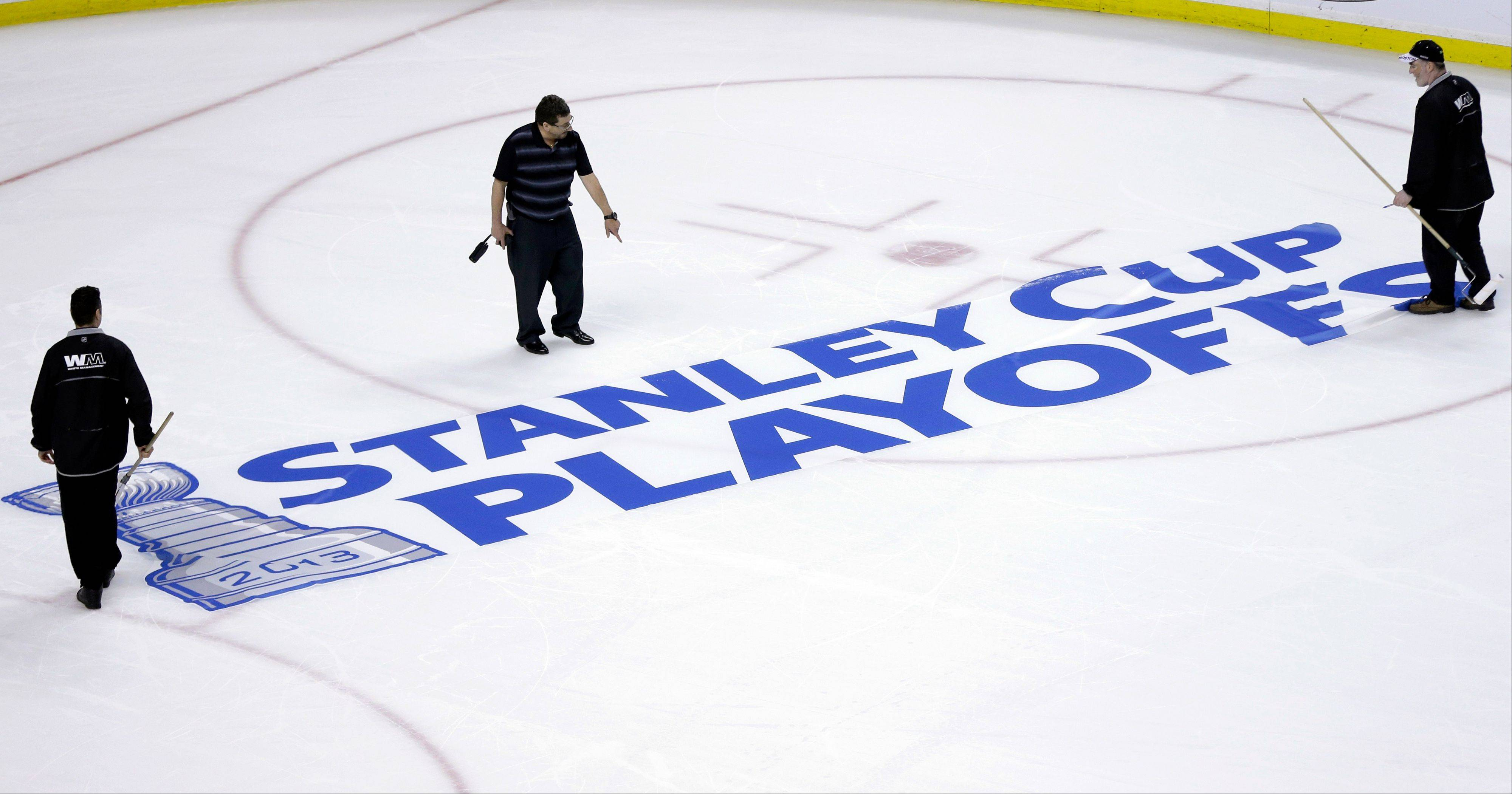 Workers position a Stanley Cup Playoffs logo onto the ice at TD Garden in Boston. The Chicago Blackhawks open their first-round series Tuesday night against the Minnesota Wild at the United Center.