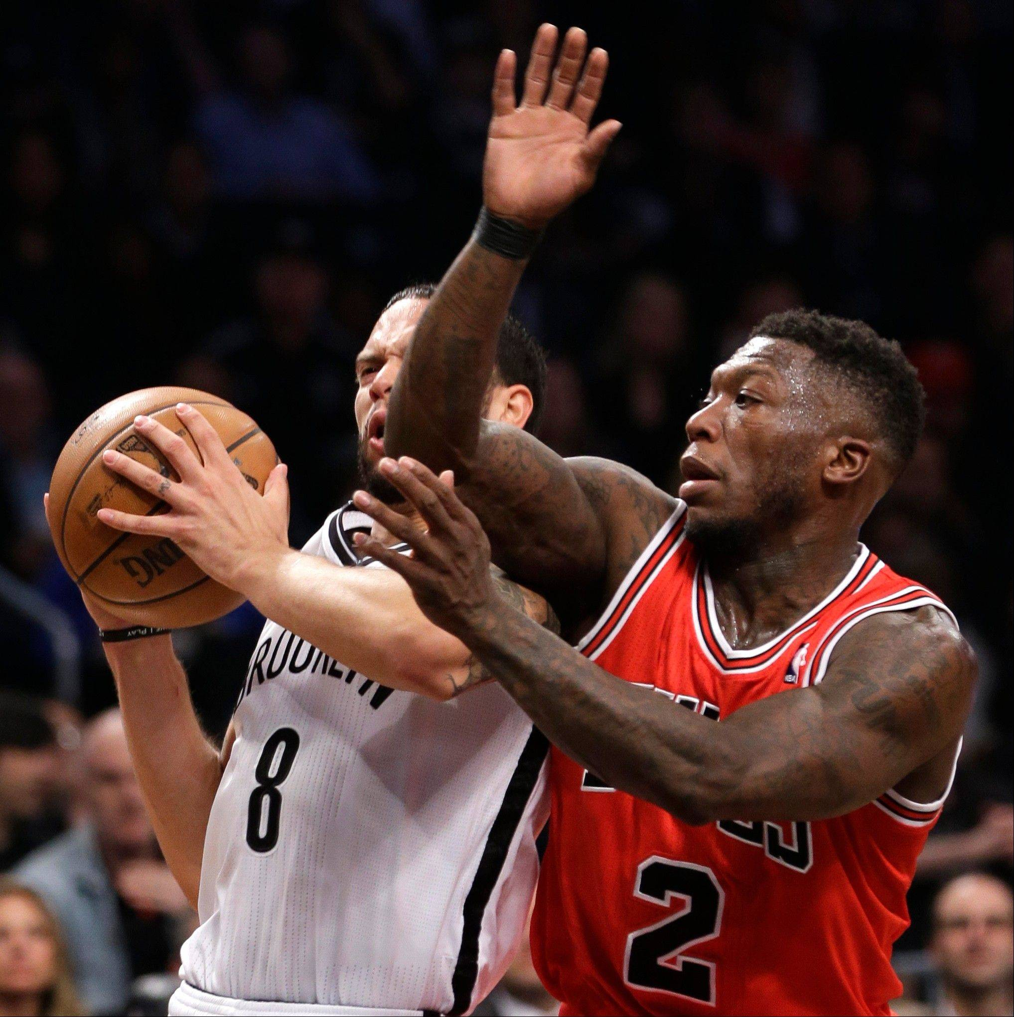 Brooklyn Nets guard Deron Williams collides with Nate Robinson as he drives toward the basket in the first half of Game 5 in New York on Monday.