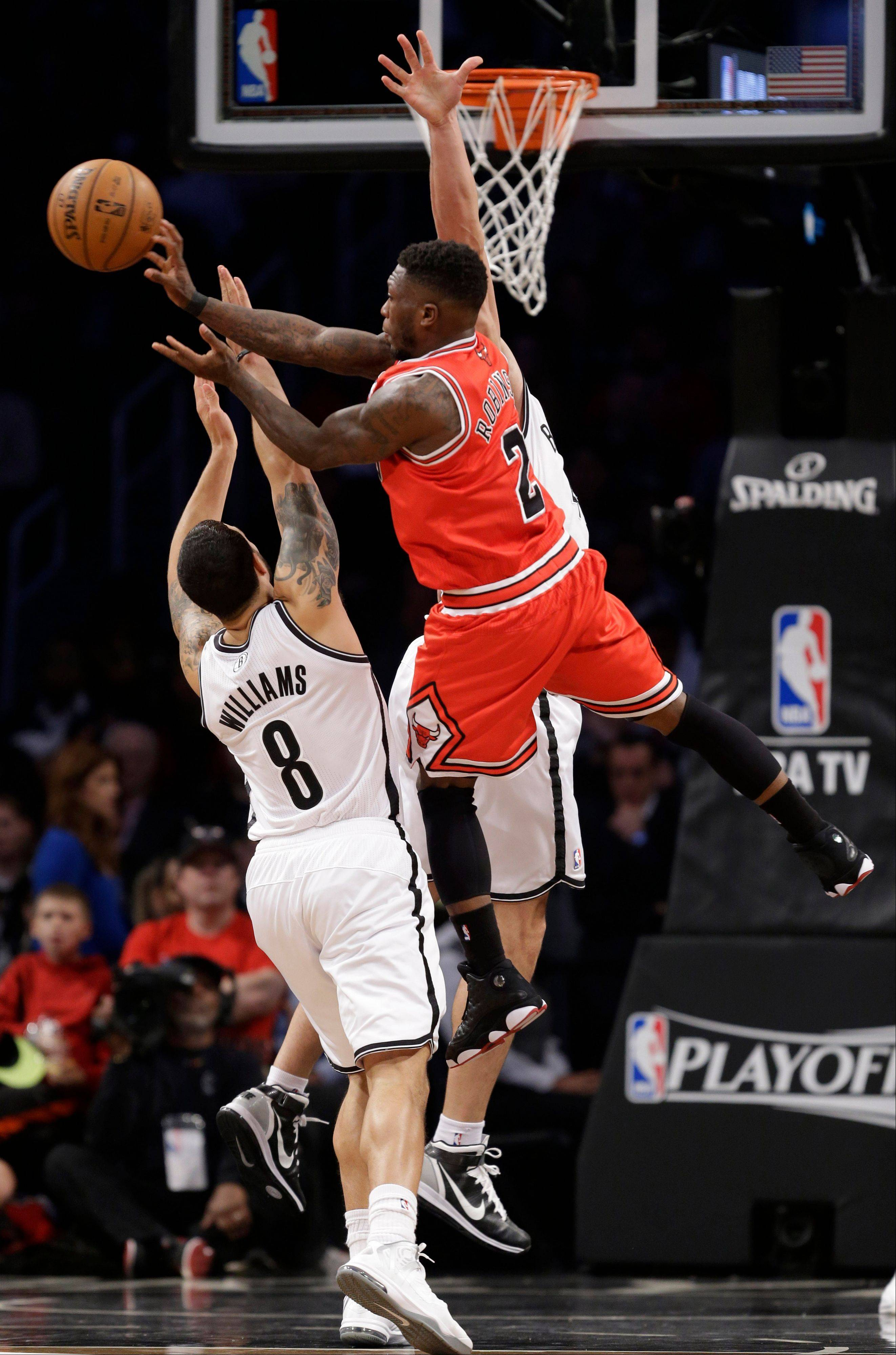 Bulls guard Nate Robinson (2) passes over the defense of Brooklyn Nets guard Deron Williams (8) in the first half of Game 5 of their first-round NBA basketball playoff series, Monday, April 29, 2013, in New York.