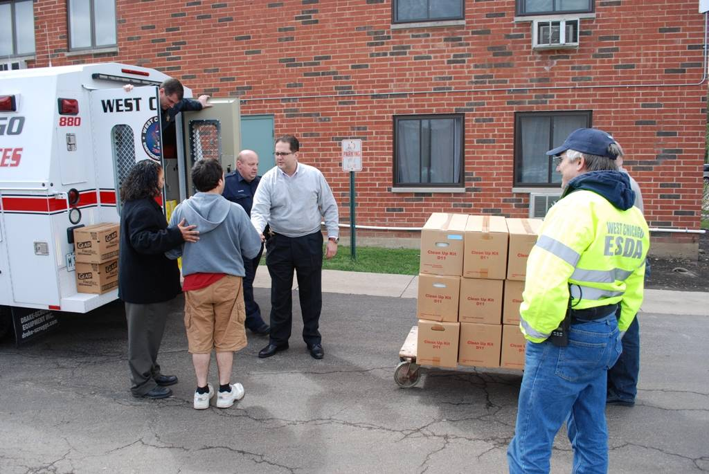 West Chicago Police Chief Laz Perez (center shaking hands) and ESDA Director Steve Gottlieb (wearing vest) assist a Town & Country Apartment resident by providing an American Red Cross cleanup kit.