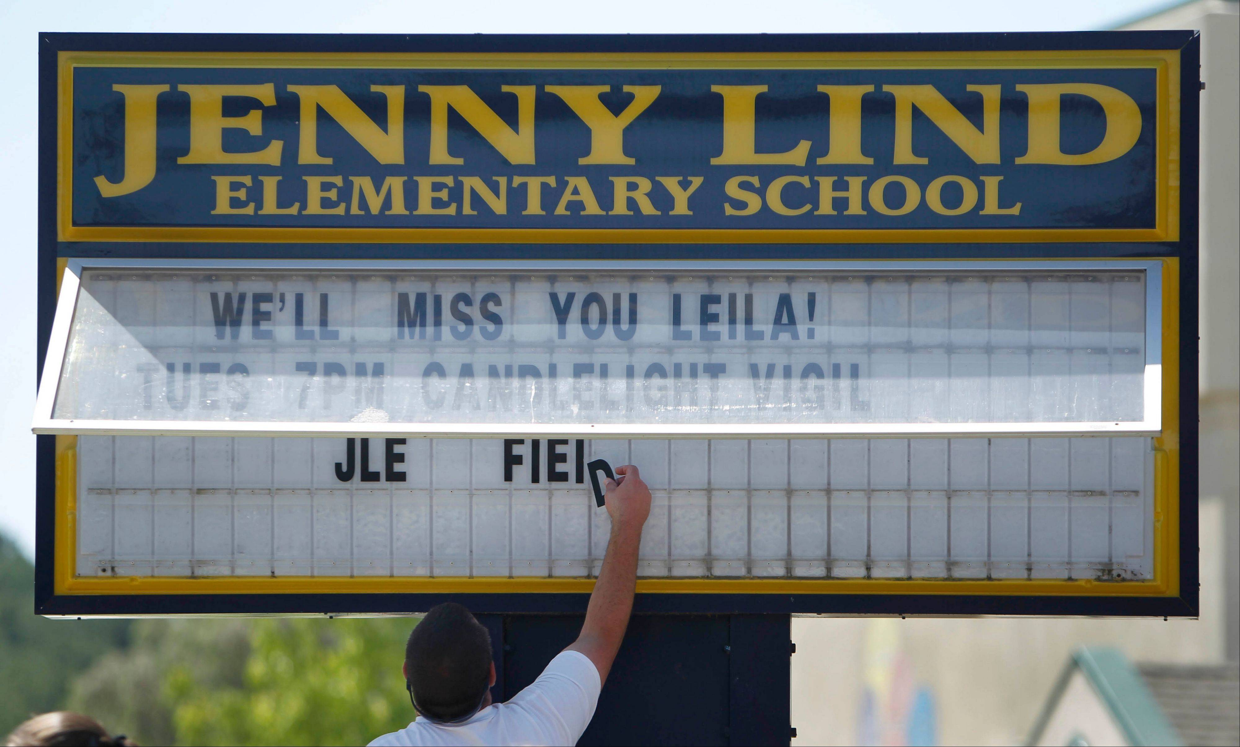 Patrick Foley, head custodian at Jenny Lind Elementary School, puts up a sign about a candlelight vigil to be help for Leila Fowler, in Valley Springs, Calif., Monday, April 29, 2013. Authorities are searching for the killer of Fowler, 8, a third-grader at Jenny Lind, who was found dead by her 12-year-old brother in the family's Valley Springs home Saturday.